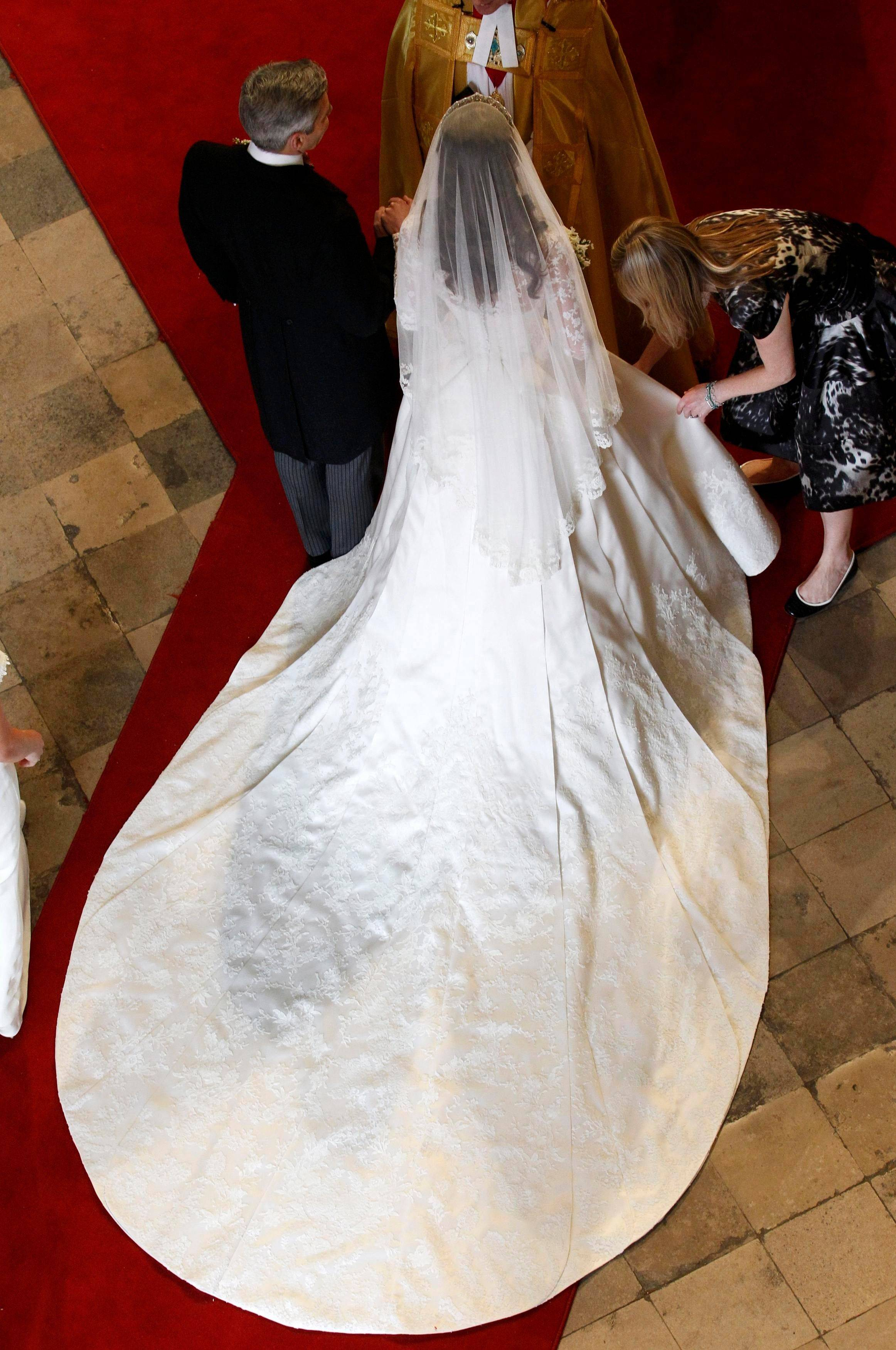Kate Middleton has her dress adjusted as she arrives with her father Michael at Westminster Abbey before her marriage to Britain's Prince William in central London April 29, 2011.