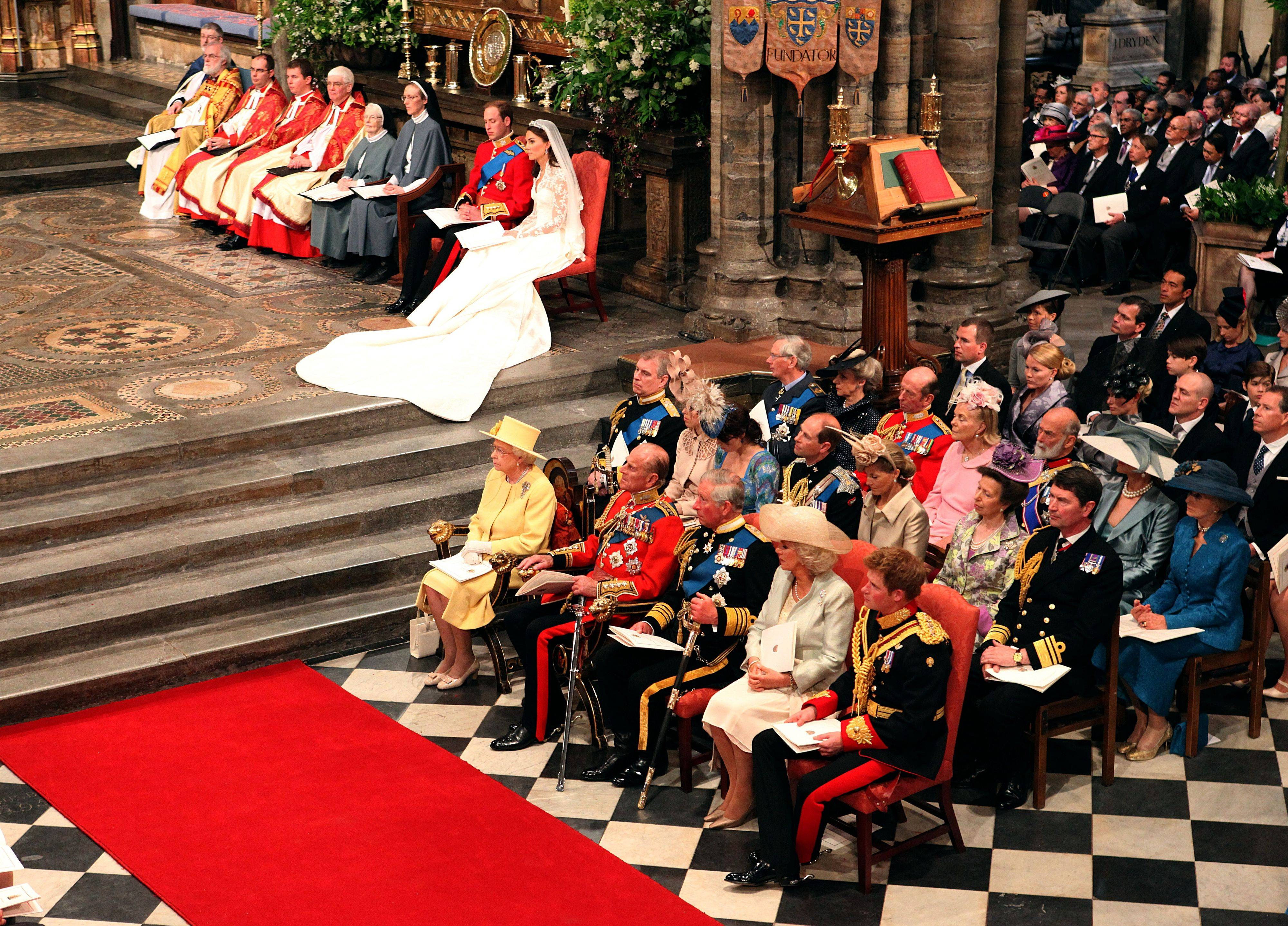 Reverend Richard Chartres, Lord Bishop of London, unseen, reads from the pulpit, watched by Prince William and his bride Kate Middleton, right, during their wedding service at London's Westminster Abbey.