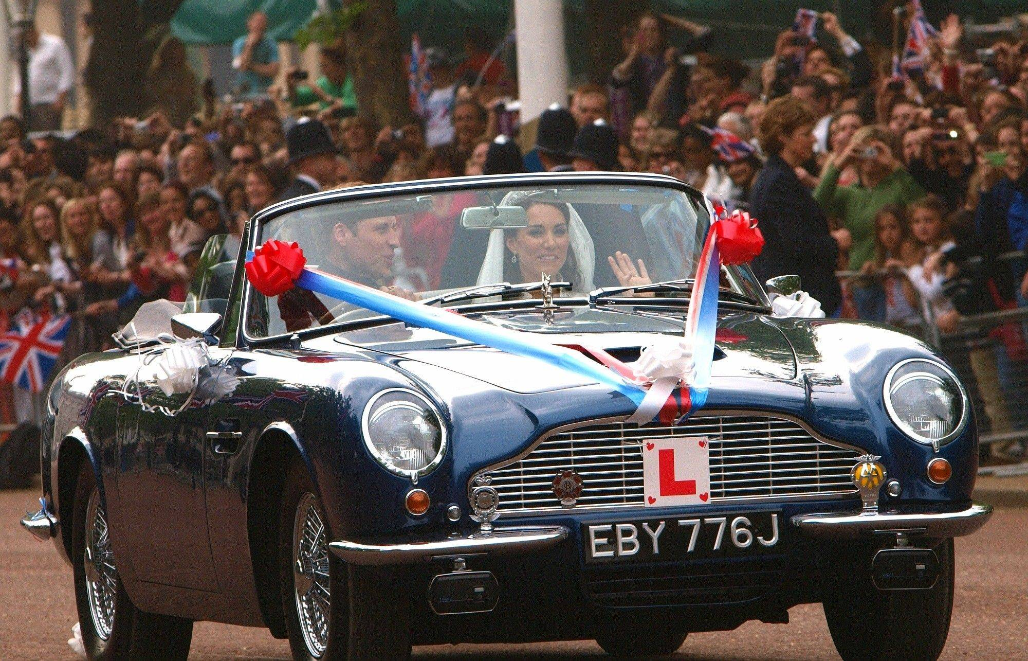 Britain's Prince William drives his wife, Kate, Duchess of Cambridge on The Mall in London in his father Prince Charles' Aston Martin Volante sports car covered with bunting on their way to Clarence House after their wedding in nearby Westminster Abbey, in London Friday April 29, 2011.