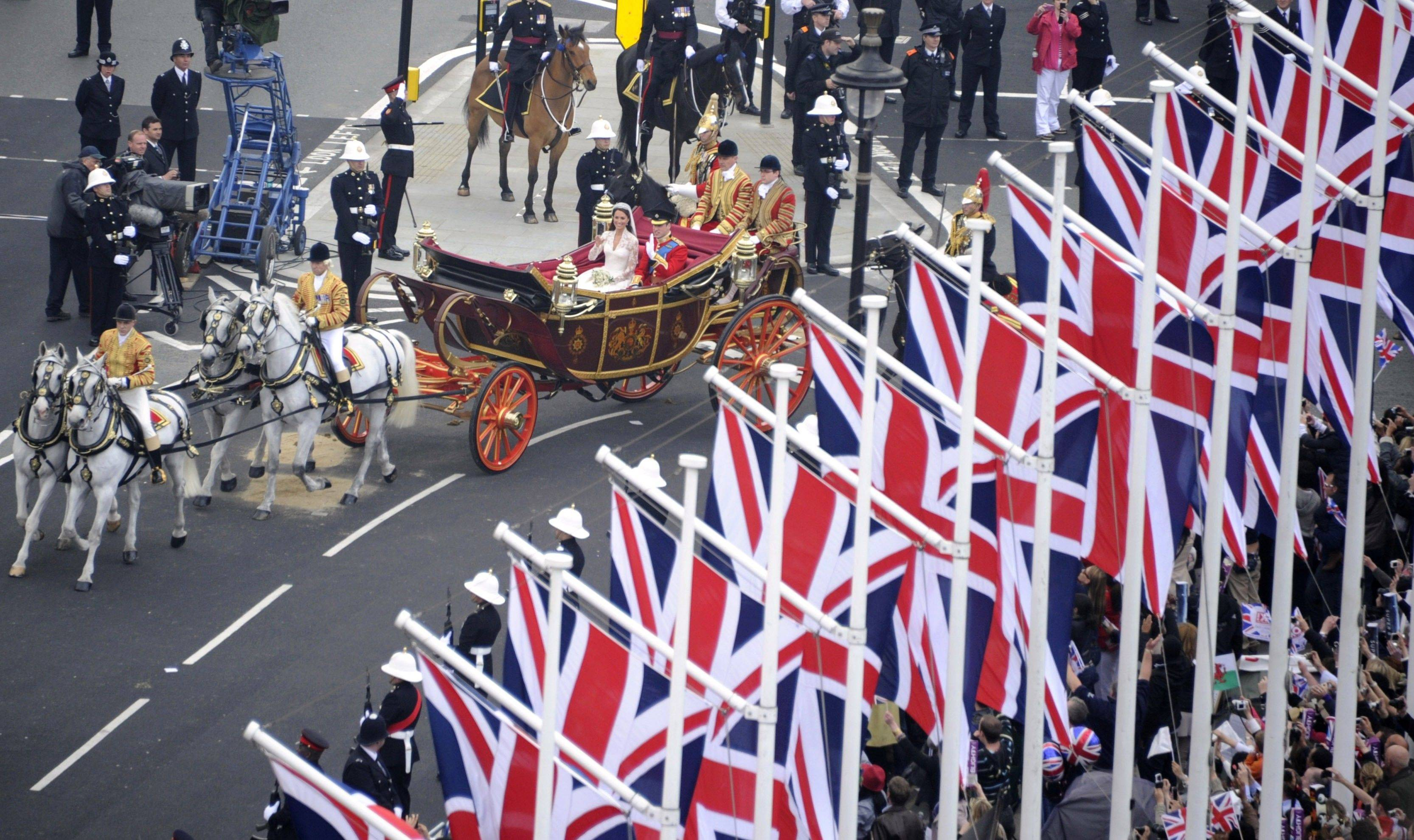 Britain's Prince William and Kate, the Duchess of Cambridge, wave as they travel in the 1902 State Landau carriage along the processional route to Buckingham Palace, London, Friday April 29, 2011.