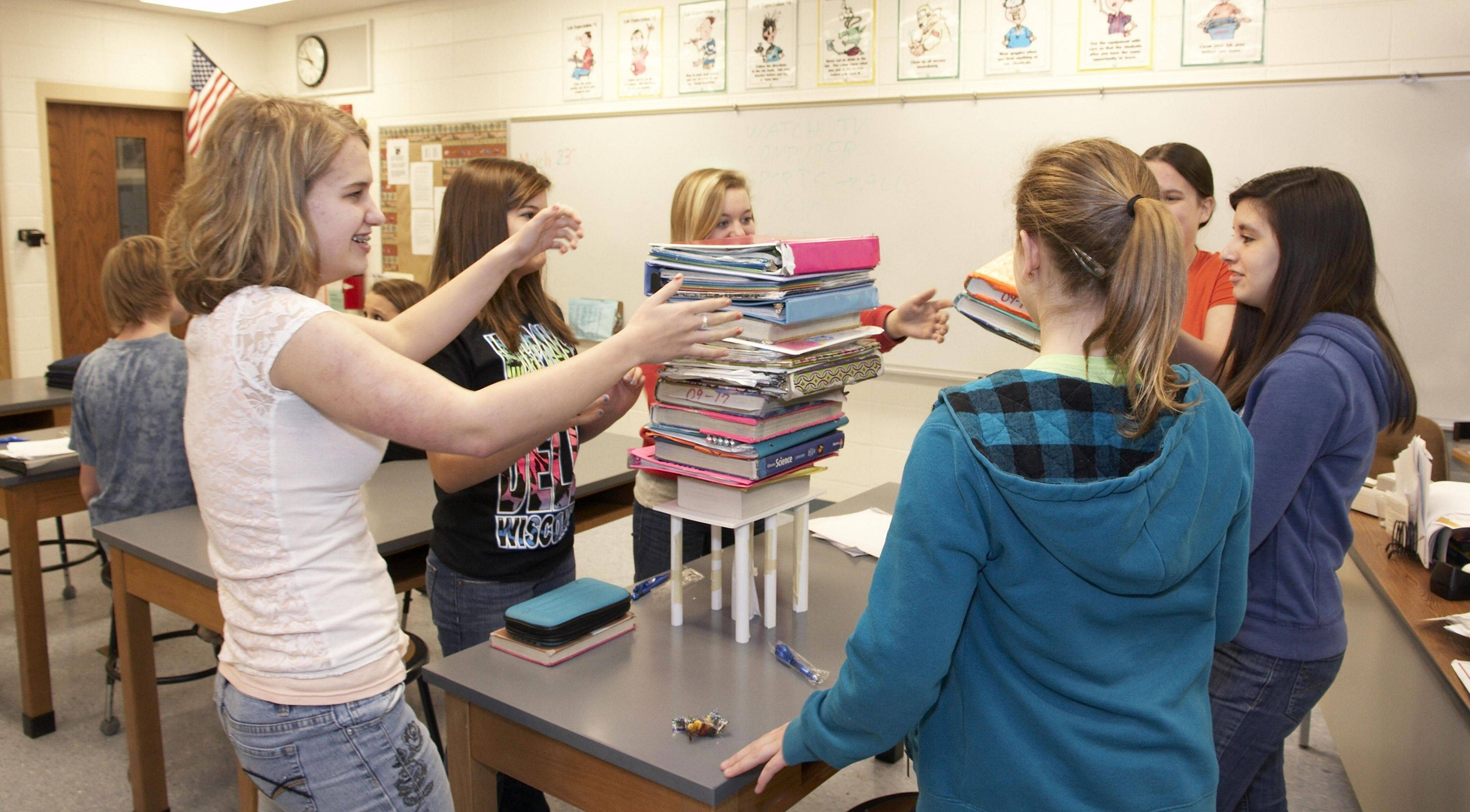 Fox River Grove Middle School students test the design of their 8-inch tall paper table.
