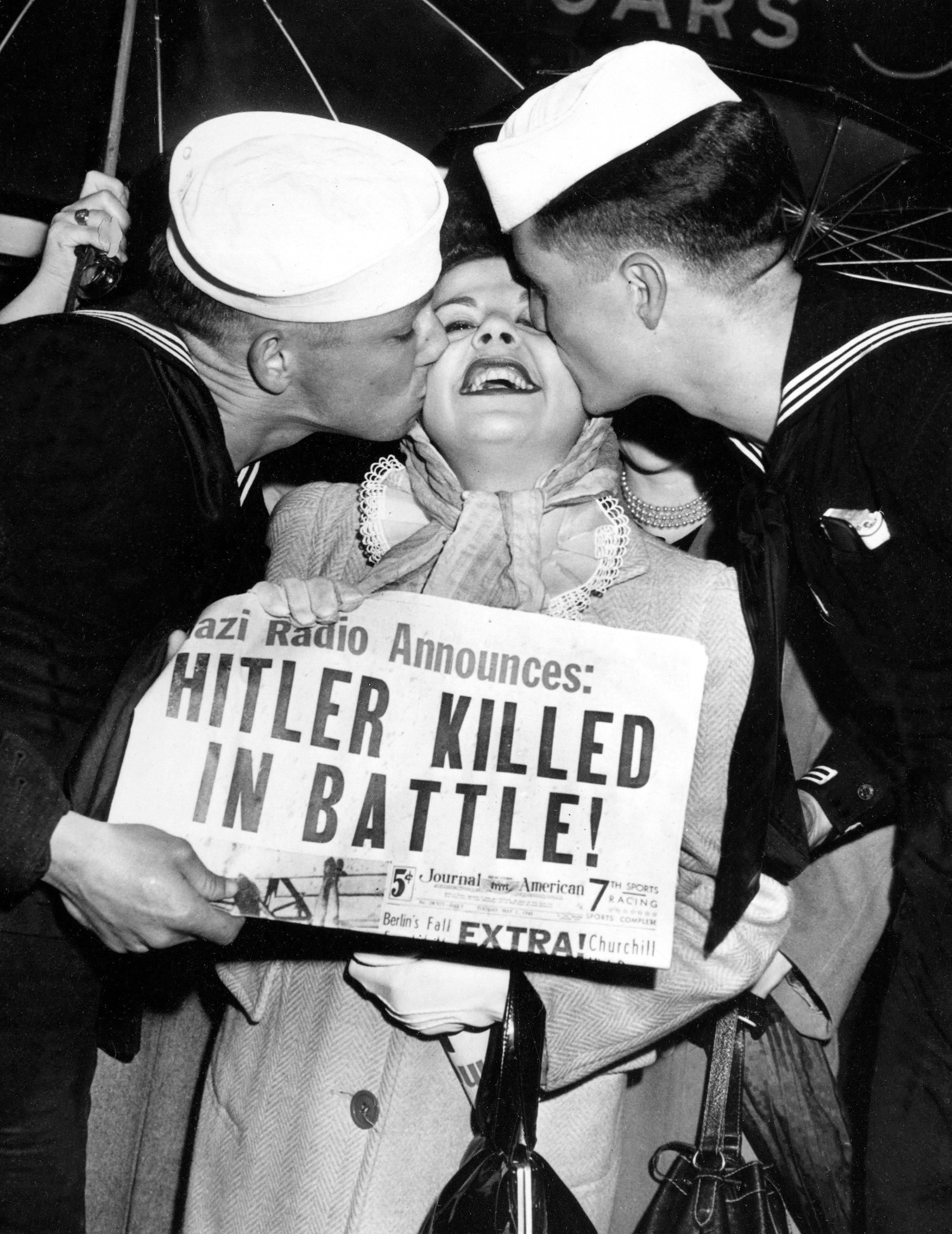 While the death of Adolf Hitler didn't lead to widespread celebration in American streets, these two U.S. sailors kiss a woman holding a newspaper announcing Hitler's death in 1945.
