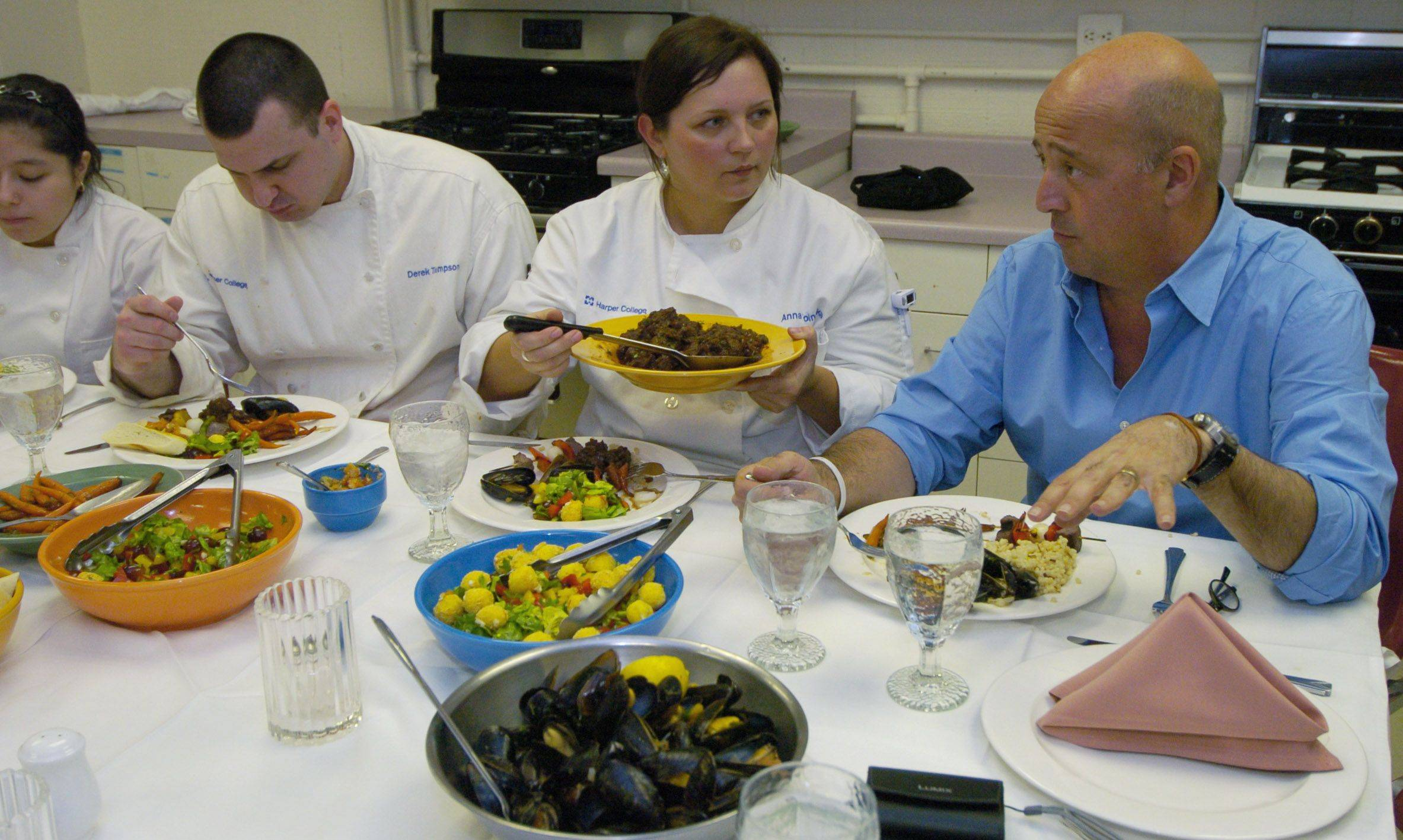 Andrew Zimmern, right, chats with Anna Woinska of Schaumburg during a dinner she and other culinary students prepared for the Travel Channel host before his presentation at Harper College in Palatine.