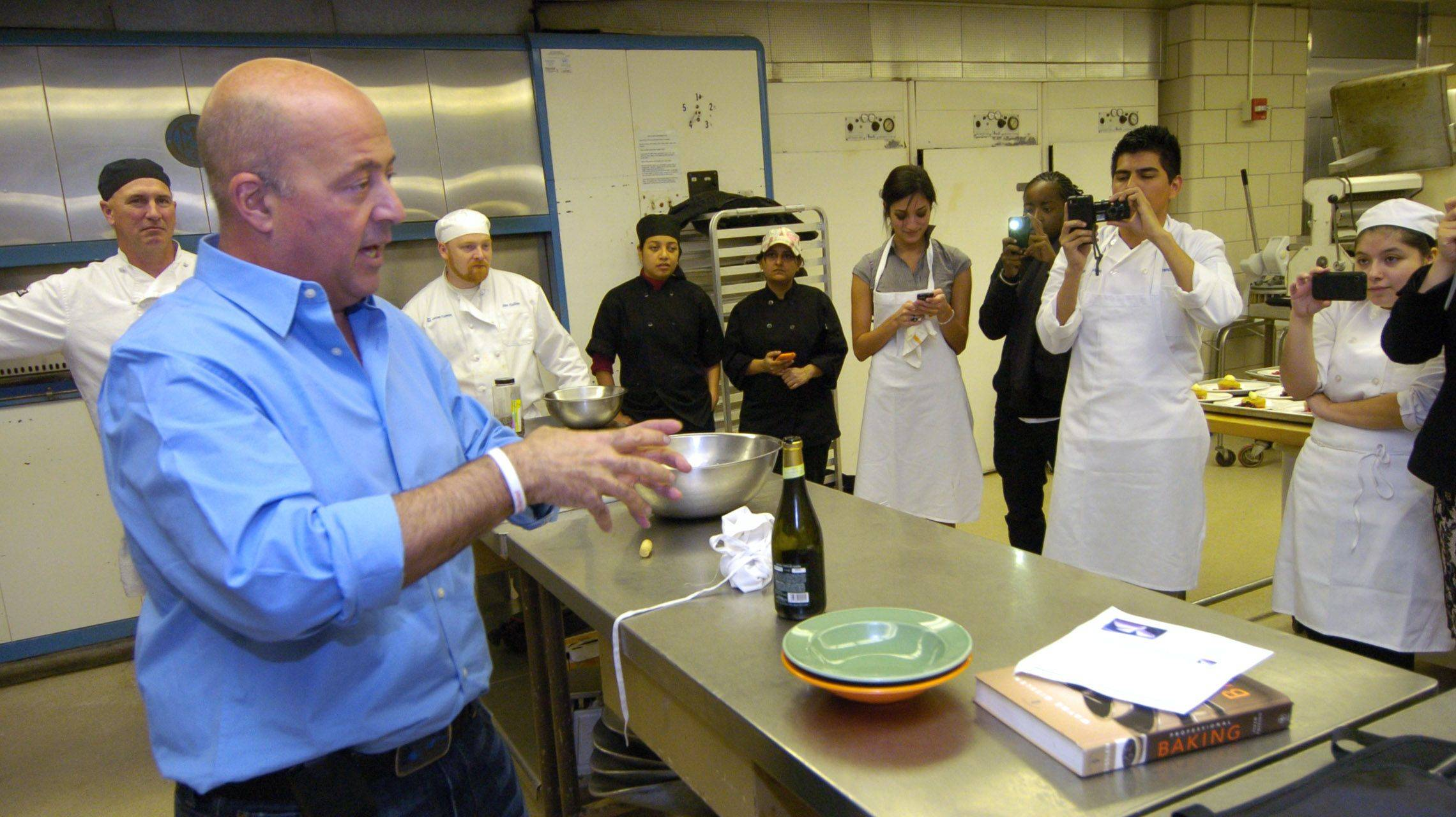 "Harper College culinary students listen as Andrew Zimmern, host of ""Bizarre Foods,"" describes how his father used to dangle him by his feet over the water so he could harvest ropes of wild mussels."