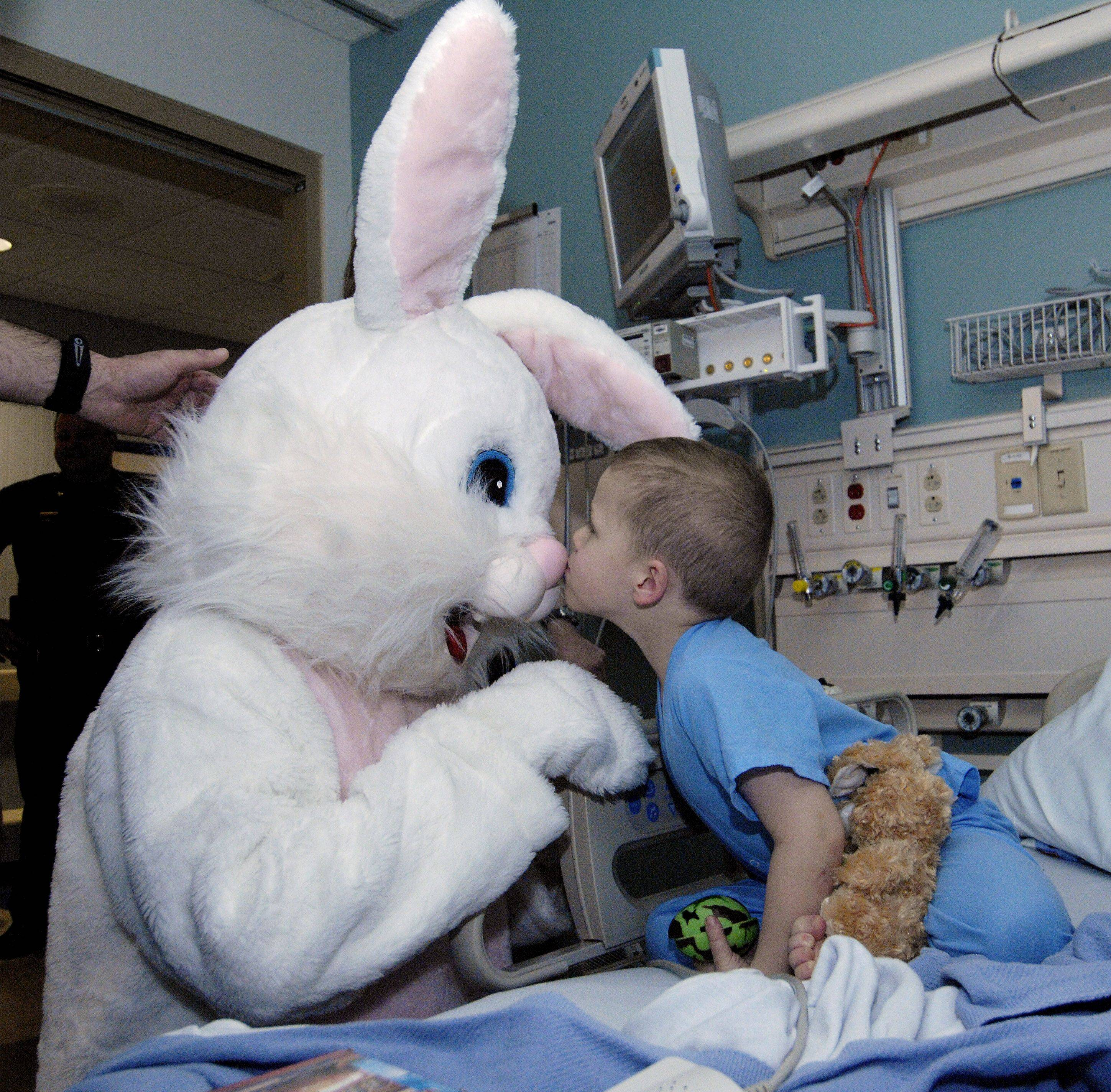 Lucas Schomas, 4 of Sugar Grove gives the Easter Bunny a kiss on the nose during a visit he recieved while in the pediatric ward of Central DuPage Hospital. The Easter Bunny visit was sponsored by DuPage County Sheriff department.
