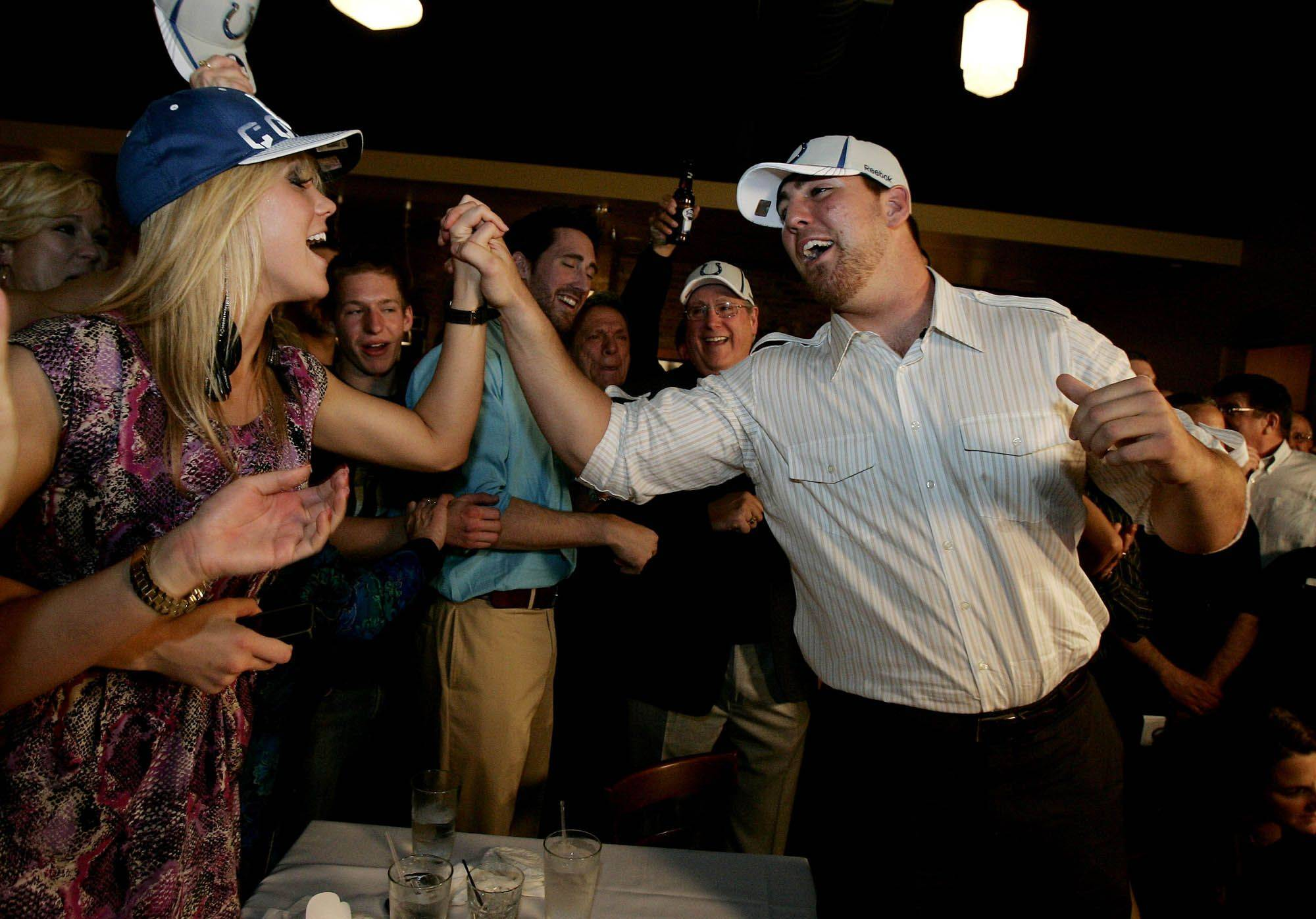 Boston College football player Anthony Castonzo from Hawthorn Woods receives a high five from his sister Kristyn as they celebrate after he was selected by the Indianapolis Colts in the first round of the NFL draft Thursday night.