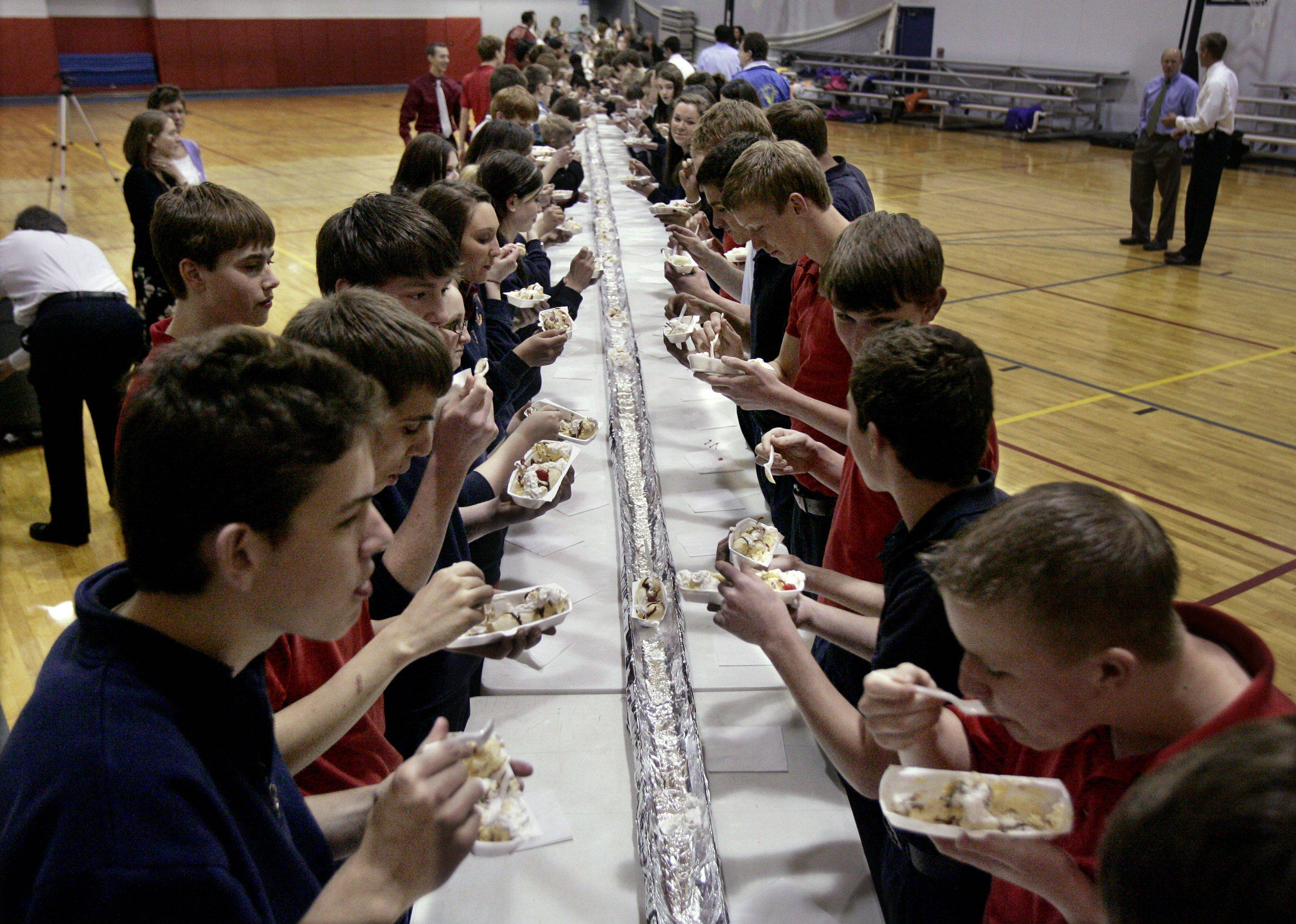 Students eat a 100-foot long banana split Monday at Quentin Road Christian School in Lake Zurich. Menards supplied a 100-foot gutter which acted as the bowl as part of the fundraiser used to purchase science and sports equipment, locker room renovations, books, and field trips.