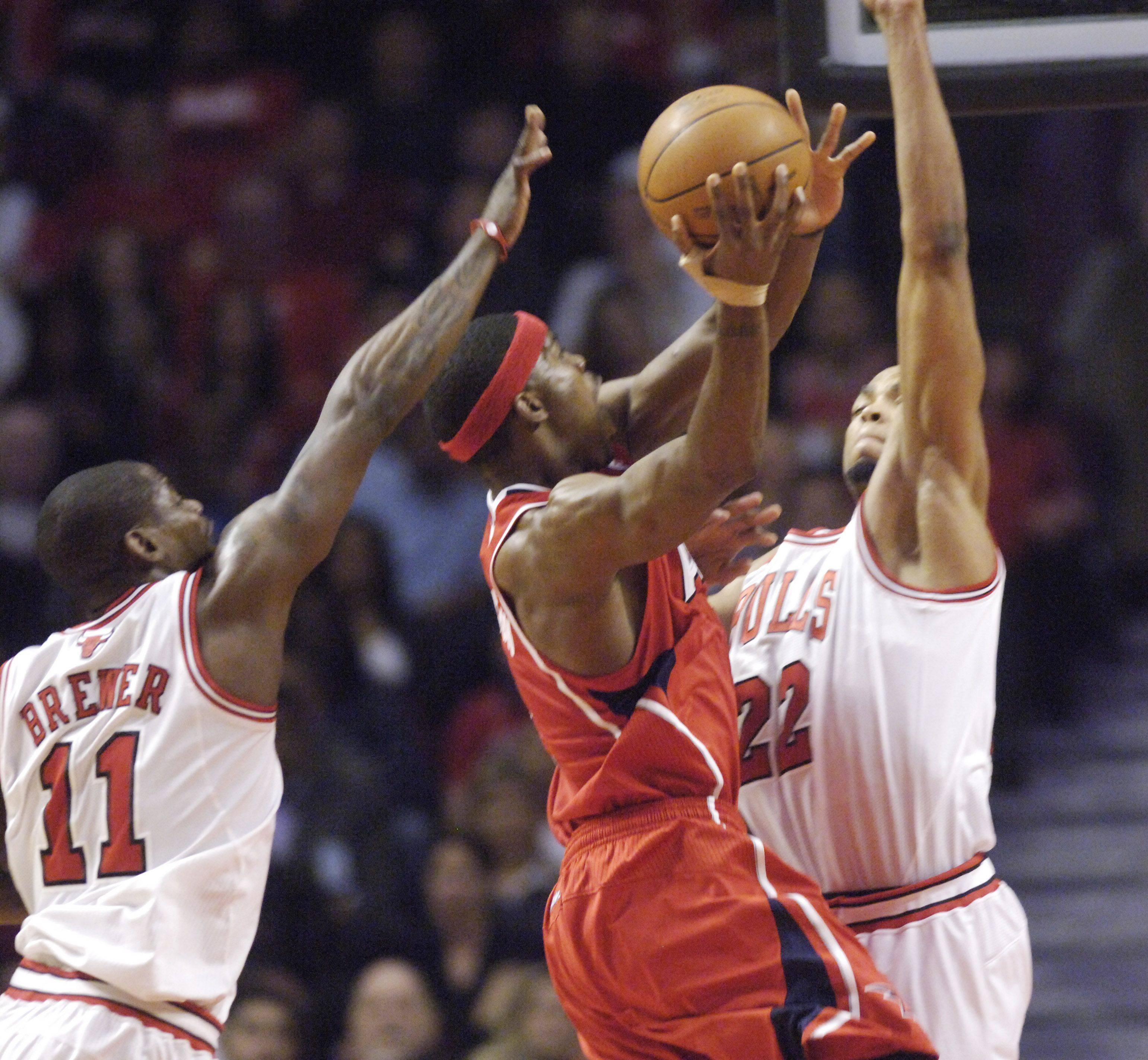 JOE LEWNARD/jlewnard@dailyherald.comJoe Johnson of the Atlanta Hawks goes to the basket against Ronnie Brewer, left, and Taj Gibson of the Bulls during Monday's game at the United Center.