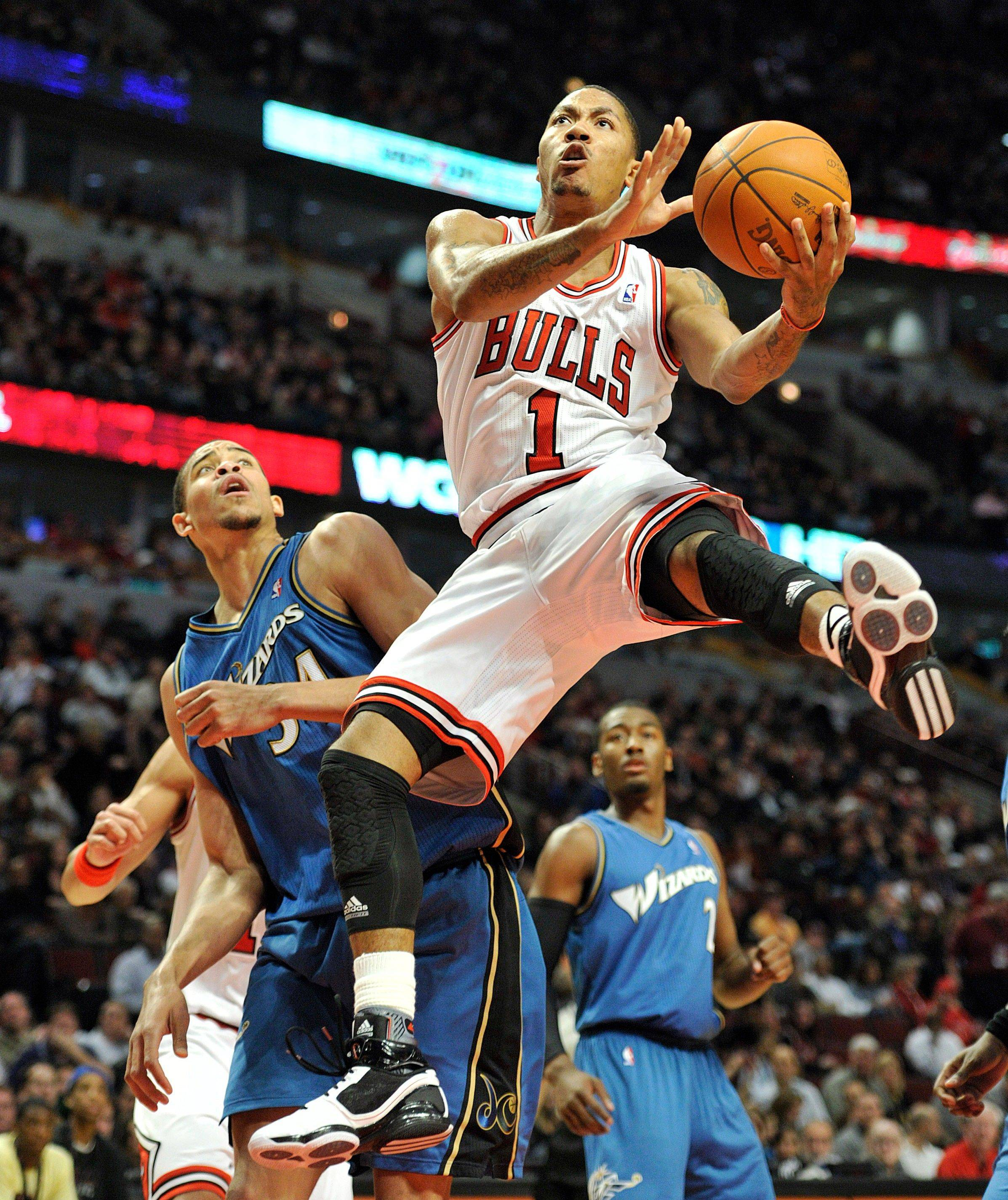 Washington Wizards' JaVale McGee left defends as the Chicago Bulls' Derrick Rose (1) drives to the basket during the second half of an NBA basketball game Saturday, Nov. 13, 2010, in Chicago. The Bulls defeated the Wizards 103-96.