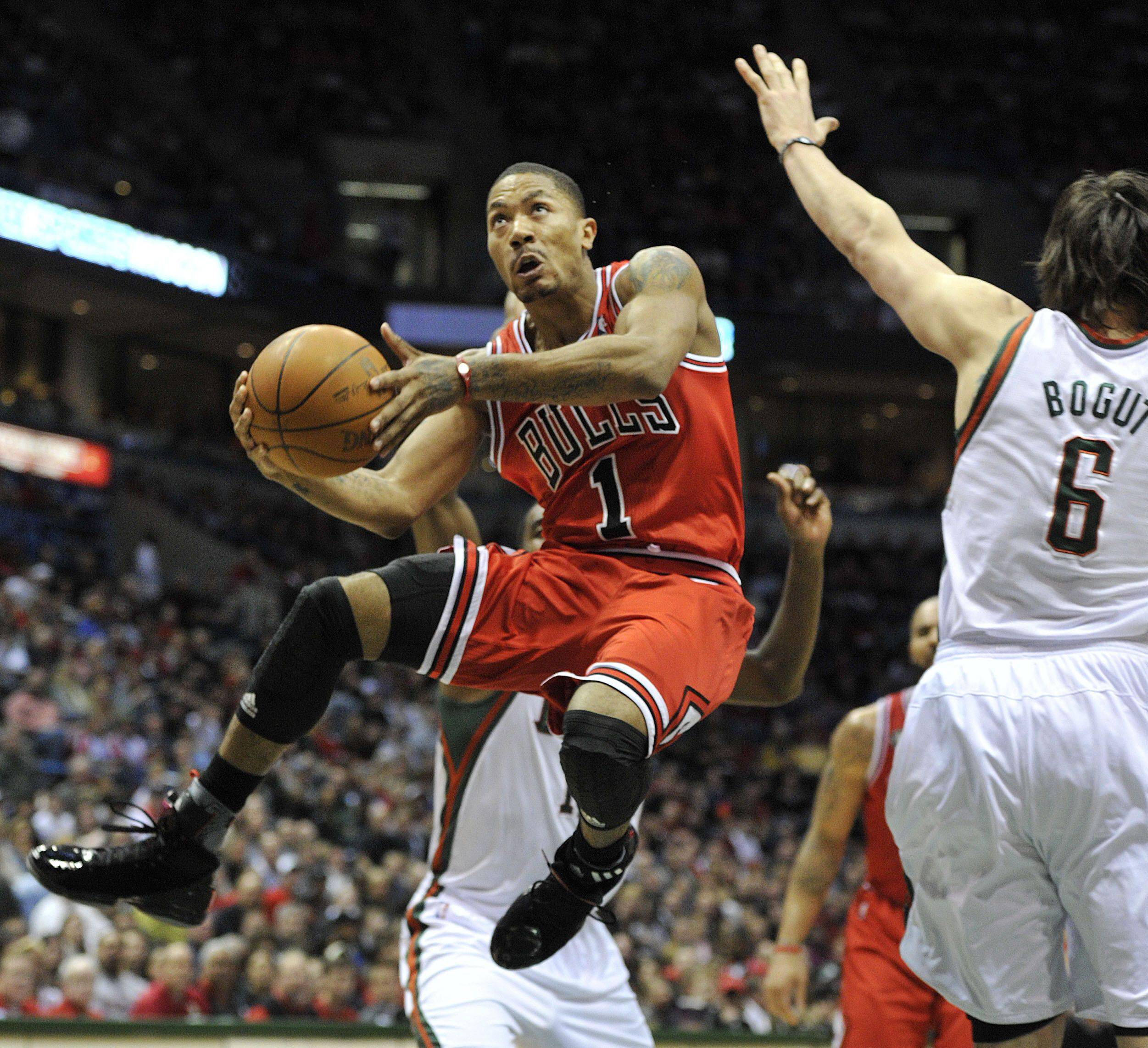 Chicago Bulls' Derrick Rose (1) drives to the basket around the Milwaukee Bucks' Andrew Bogut (6) during the first half of an NBA basketball game Saturday, March 26, 2011, in Milwaukee.