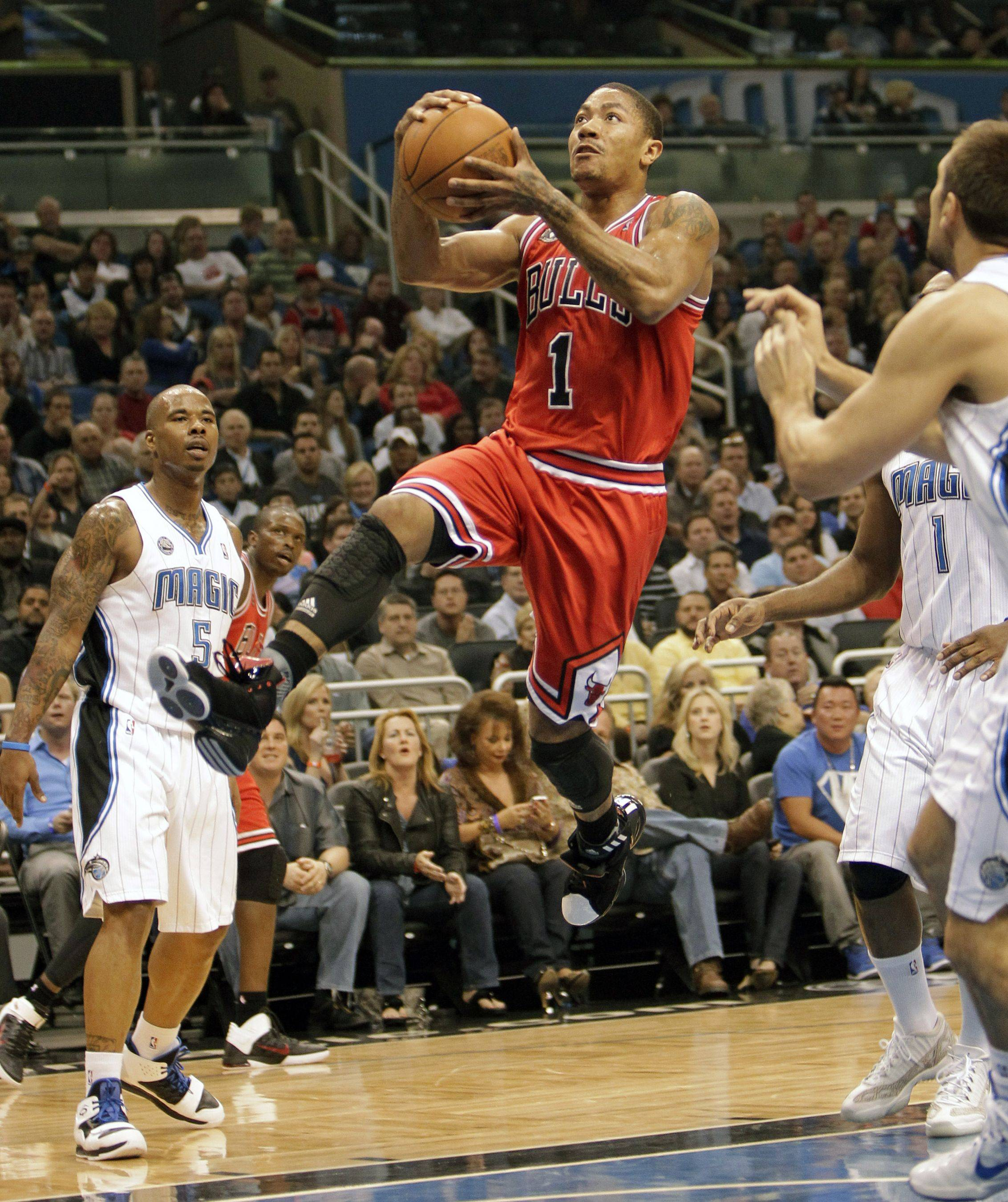 Chicago Bulls' Derrick Rose (1) gets off a shot between Orlando Magic's Quentin Richardson (5) and Ryan Anderson, right, during the first half of an NBA basketball game in Orlando, Fla., Friday, March 4, 2011.