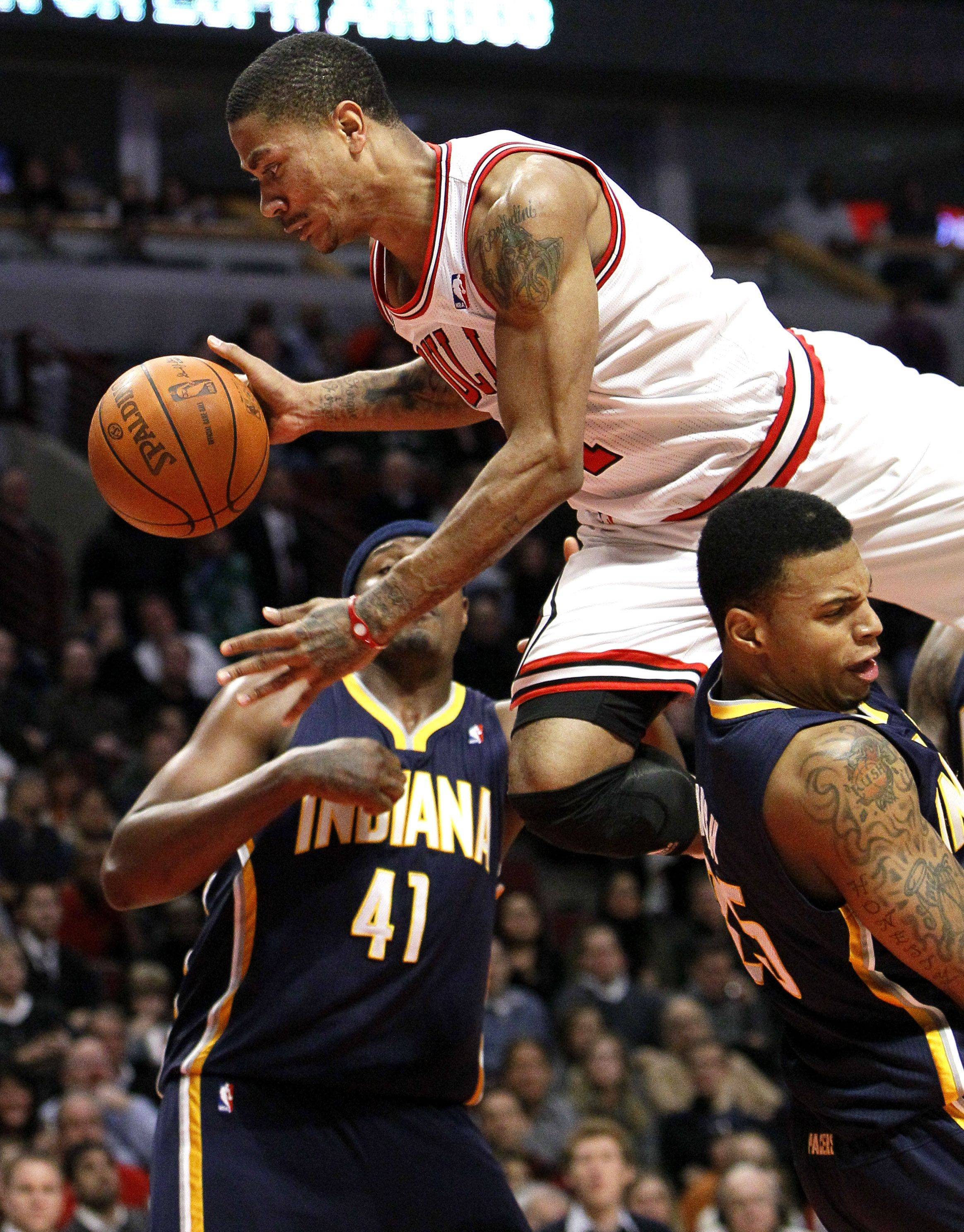 Chicago Bulls point guard Derrick Rose, center, falls over Indiana Pacers shooting guard Brandon Rush as forward James Posey watches, during the second half of an NBA basketball game Monday, Dec. 13, 2010, in Chicago. The Bulls won 92-73.