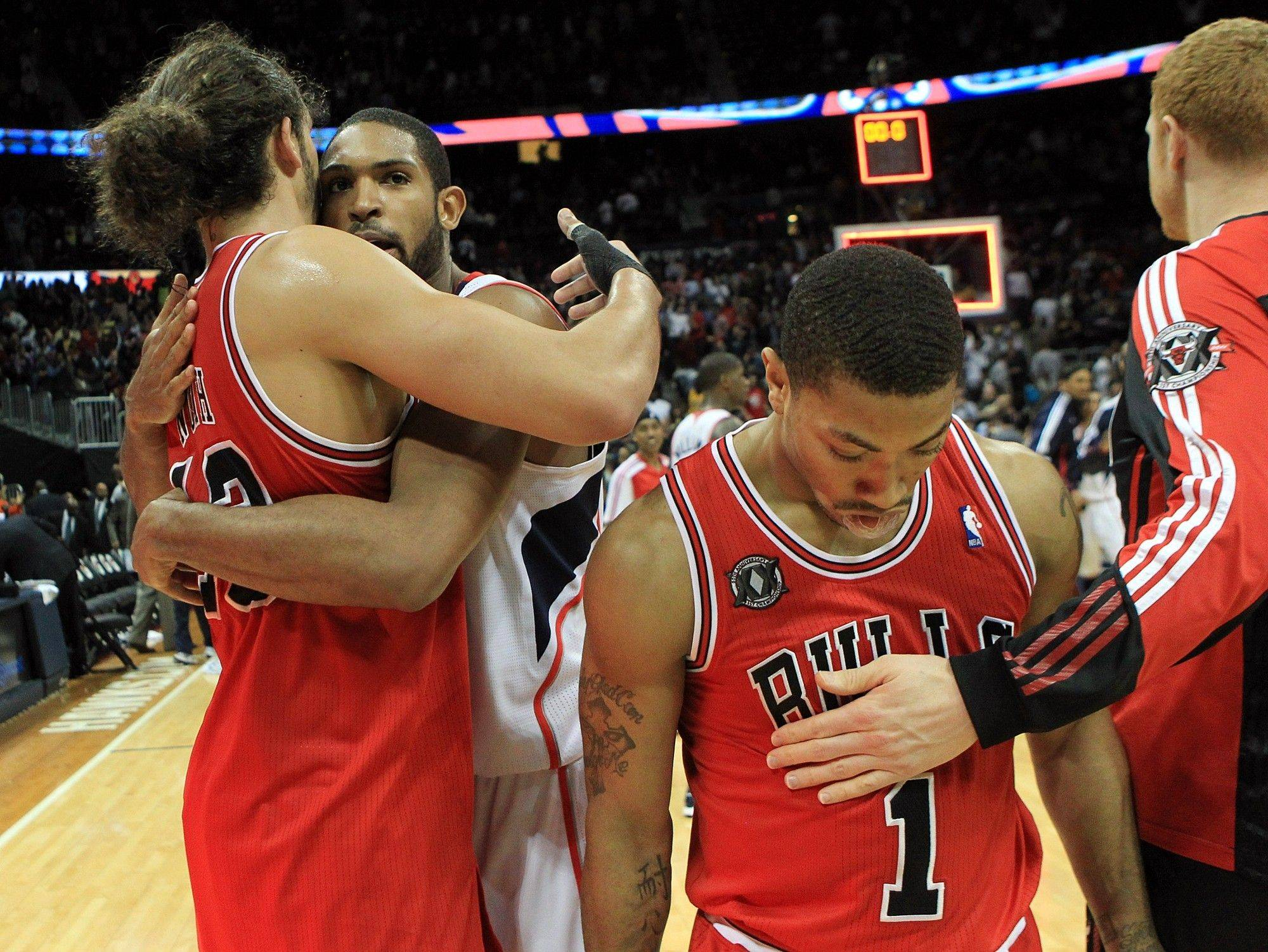 Chicago Bulls' Derrick Rose, right, walks off the court as Atlanta Hawks center Al Horford, who scored a game high 31-points, hugs Bulls' Joakim Noah, left, after an 83-30 Hawks victory in an NBA basketball game Wednesday, March 2, 2011, in Atlanta.