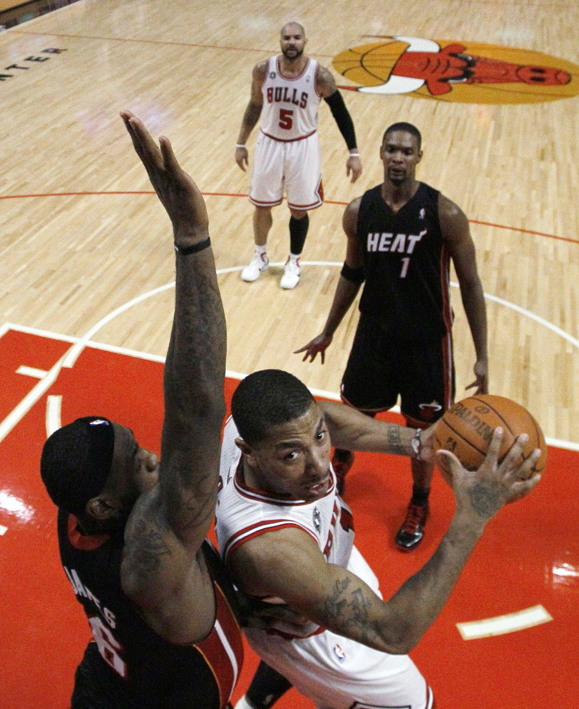 Chicago Bulls guard Derrick Rose, right, looks for a shot against Miami Heat forward LeBron James during the second half of an NBA basketball game Thursday, Feb. 24, 2011, in Chicago. The Bulls won 93-89 with Rose scoring 26 points and James 29. Watching in the background for Miami is Chris Bosh.