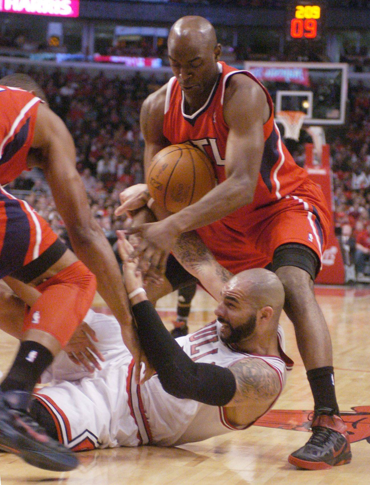 Carlos Boozer of the Bulls loses the ball as he falls between Al Horford, left, and Damien Wilkins of the Atlanta Hawks during Monday's game at the United Center.