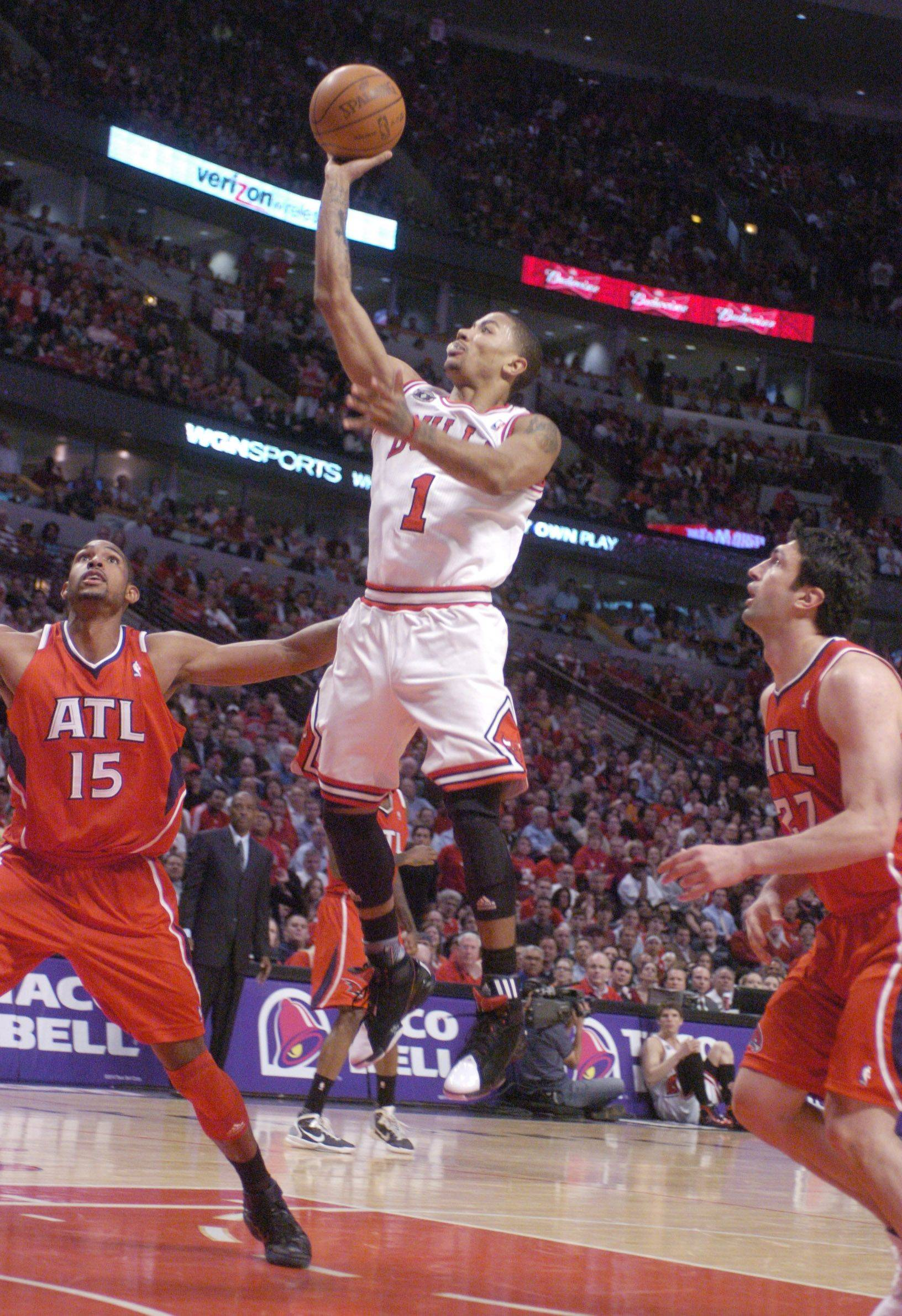 Derrick Rose of the Bulls shoots a jump shot between Al Horford, left, and Zaza Pachulia of the Atlanta Hawks during Monday's game at the United Center.