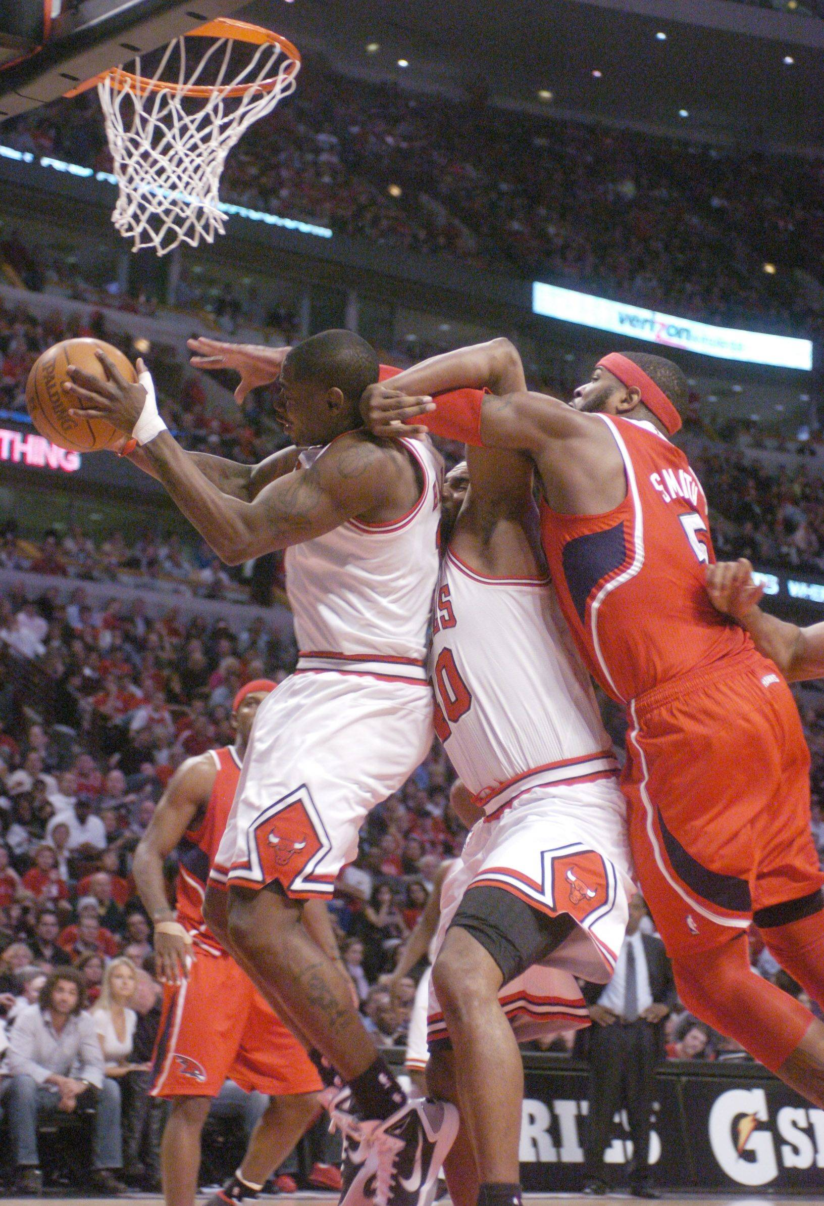 Ronnie Brewer of the Bulls draws a flagrant foul from Atlanta's Josh Smith as Kurt Thomas gets sandwiched on the play at the United Center.