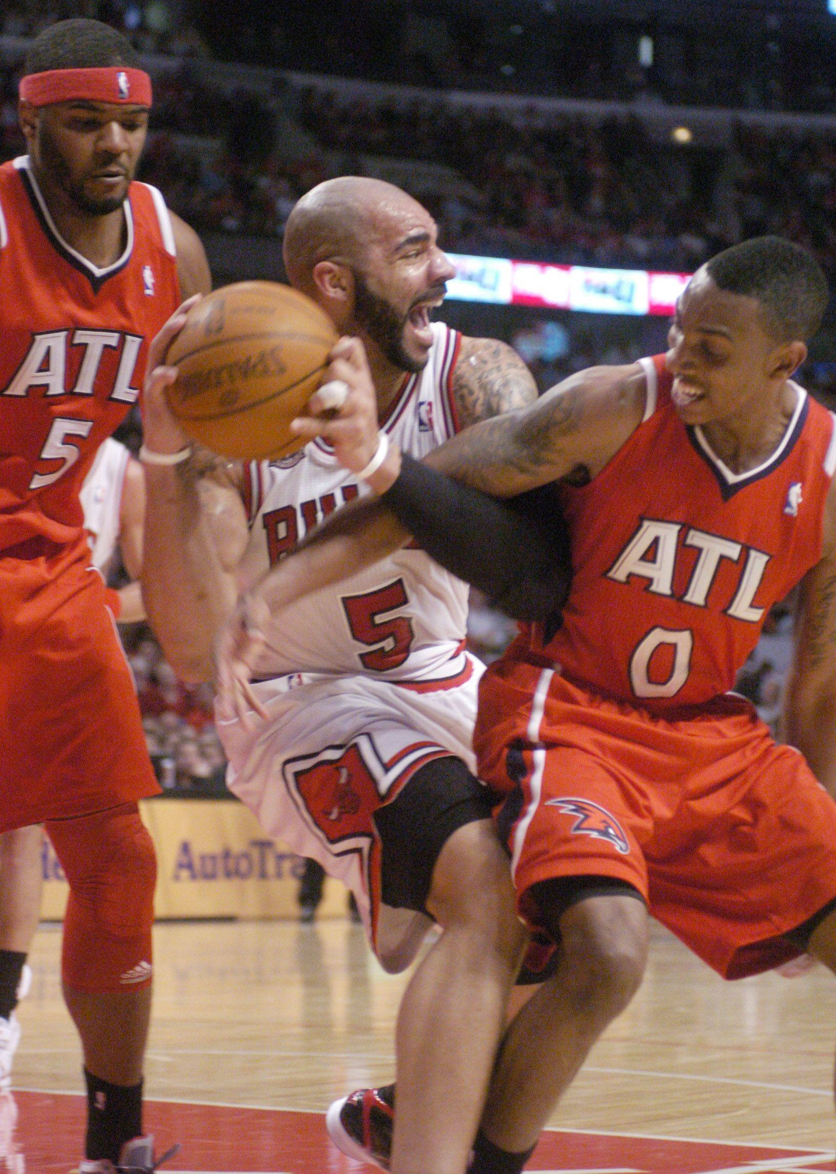 Carlos Boozer gets fouled by Jeff Teague of the Hawks, right, as Josh Smith provides coverage Monday.