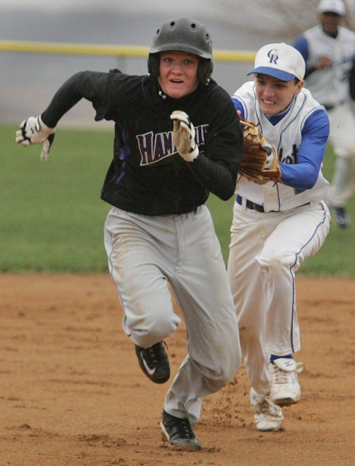 Burlington Central's Brian Leist chases down Hampshire base runner Chase Lundry for the out between second and third base.
