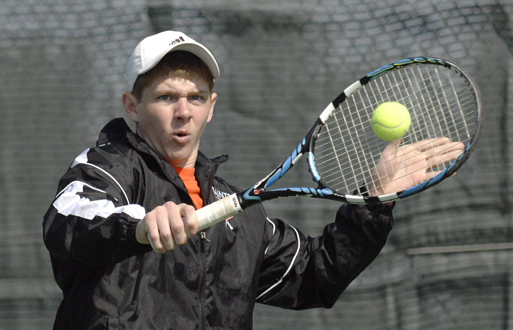 St. Charles East's Mike Muir returns a shot in his second doubles match Saturday.