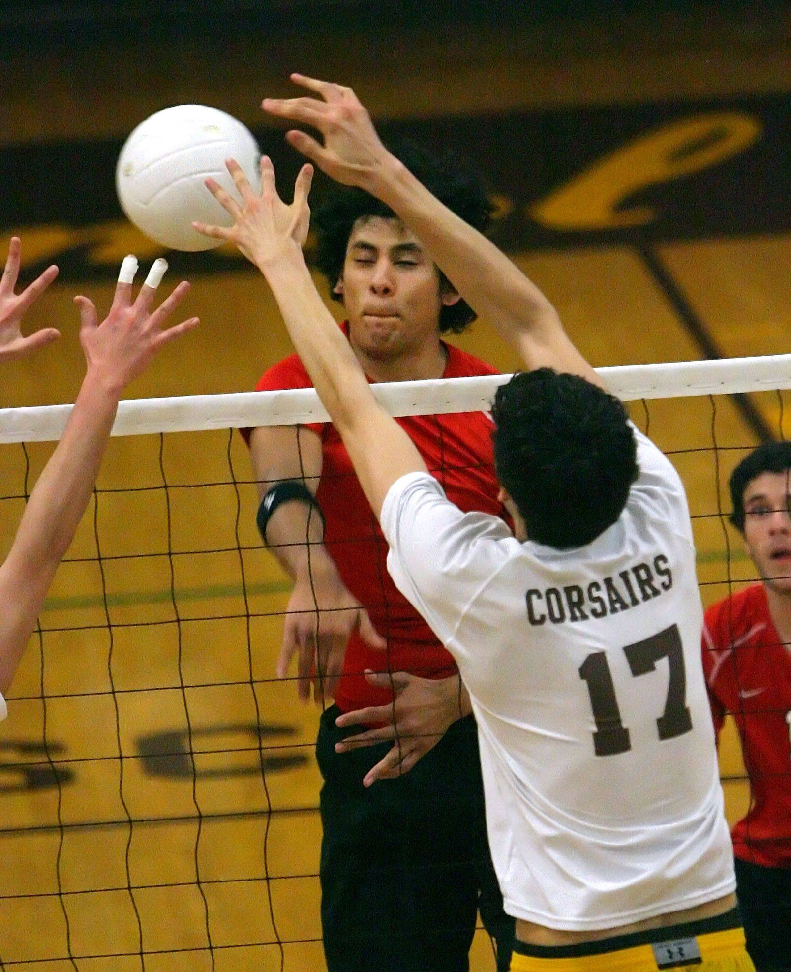 Mundelein's Jaime Jahen spikes one past Carmel's Will Collazo Monday night at Carmel High School.