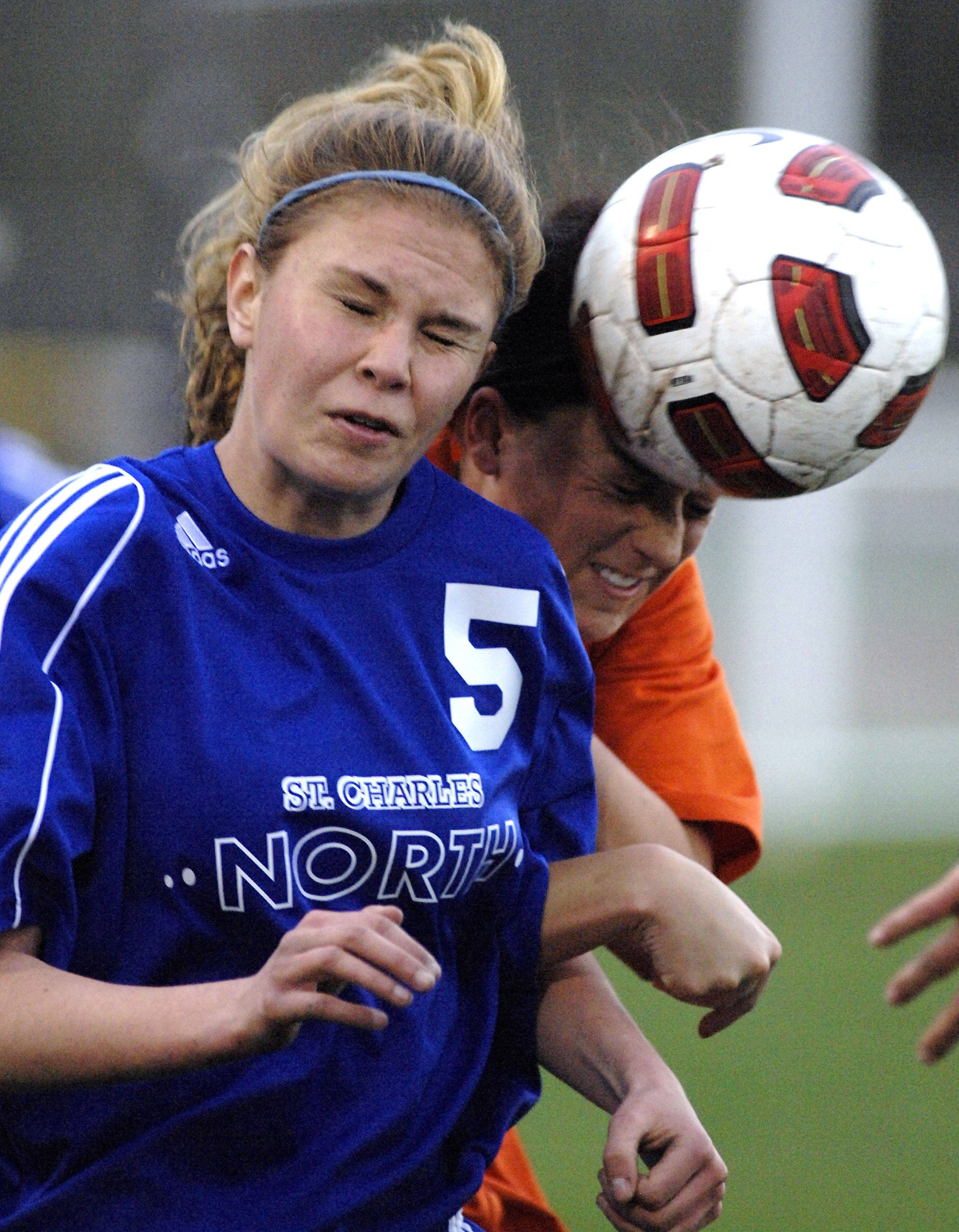 St. Charles North's Melissa Bronke and St. Charles East's Kate Rosignal fight for the ball in the first half Tuesday.