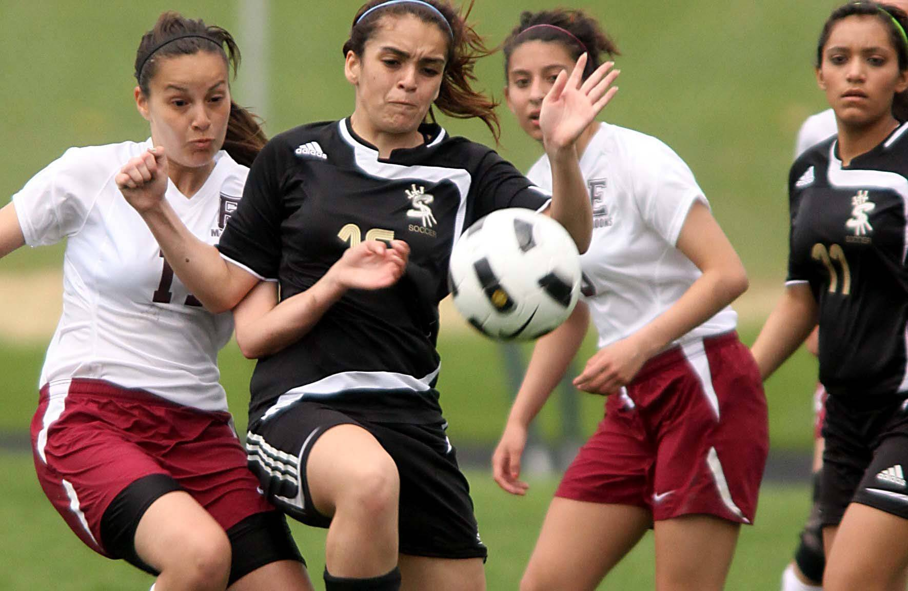 Lisette Sanchez of Elgin and Sharice Ellenwood of Streamwood battle for the ball Tuesday. At center right is Elgin's Jennifer Lopez, and at far right is Streamwood's Joceline Jimenez.