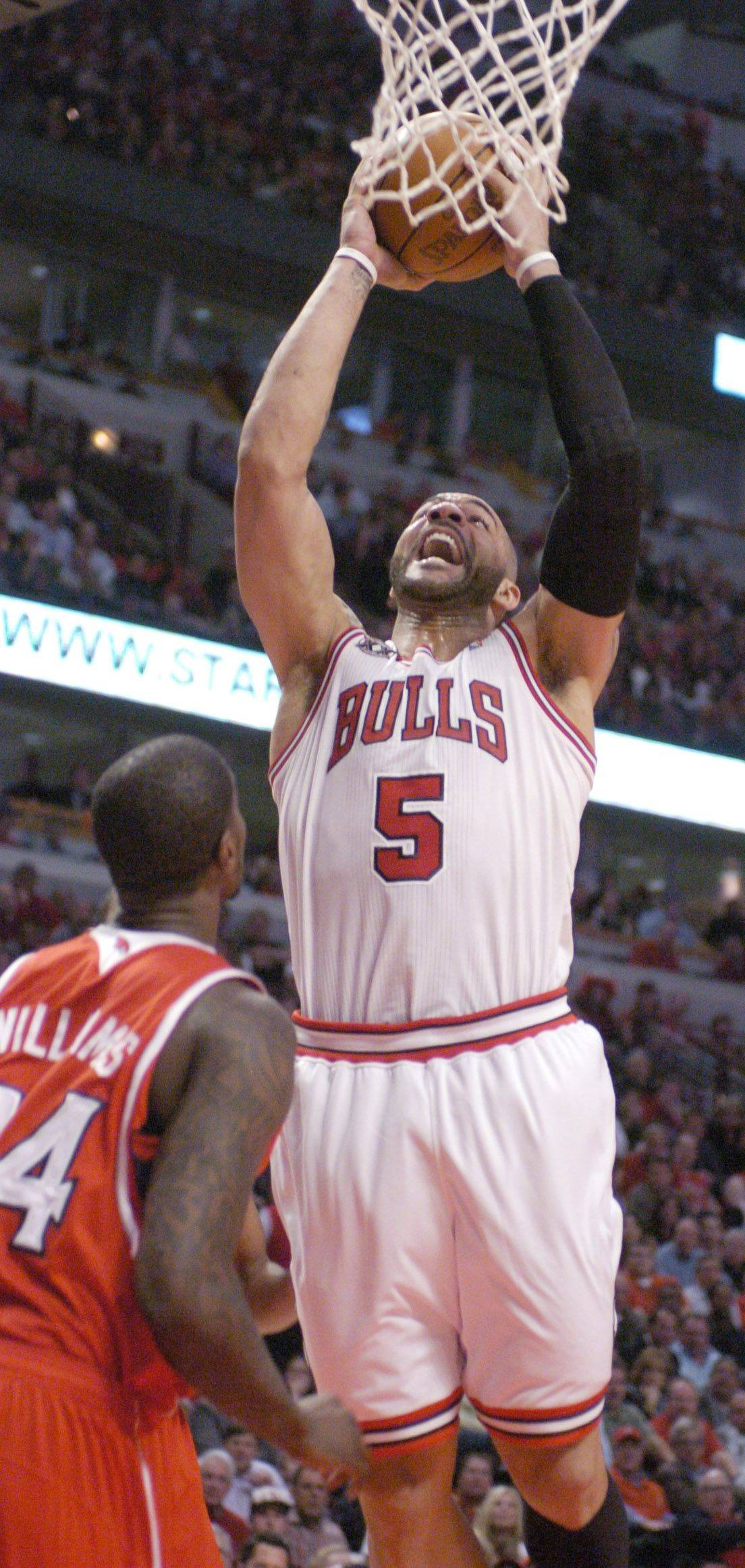 Carlos Boozer of the Bulls goes strong to the basket in front of Marvin Williams of the Hawks.