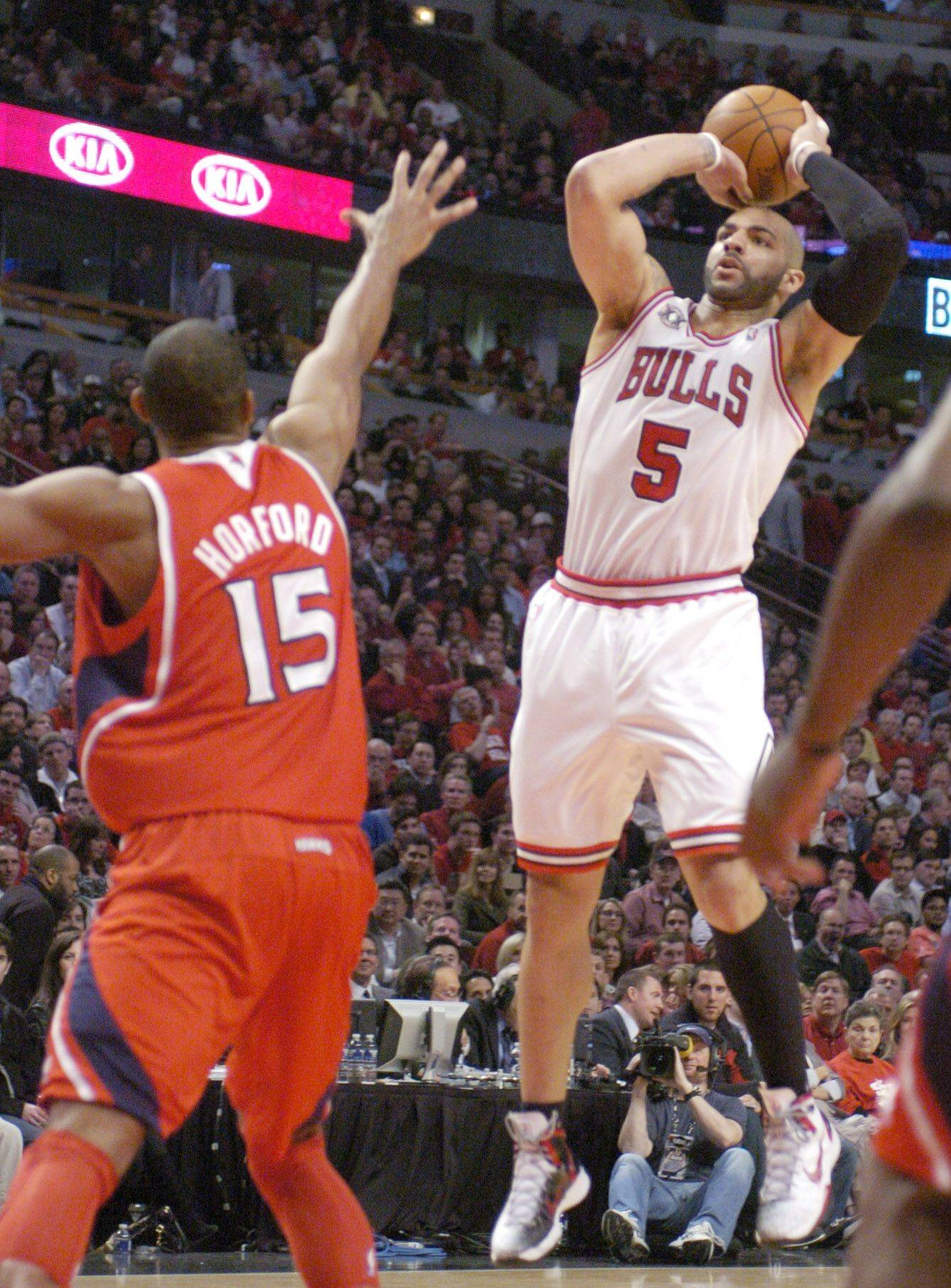 Al Horford of the Hawks tries to get a hand up as Carlos Boozer shoots a jump shot.