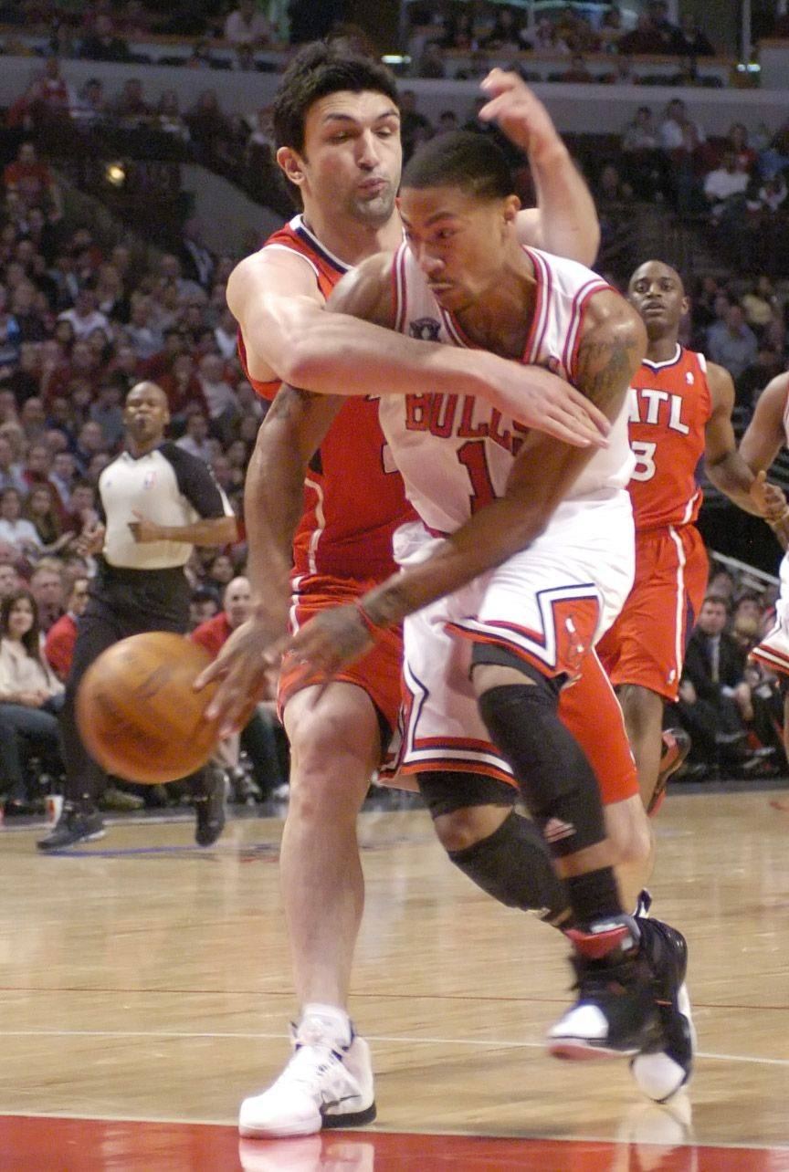 Derrick Rose is fouled by Zaza Pachulia of the Hawks as he drives in the lane during Wednesday's game.
