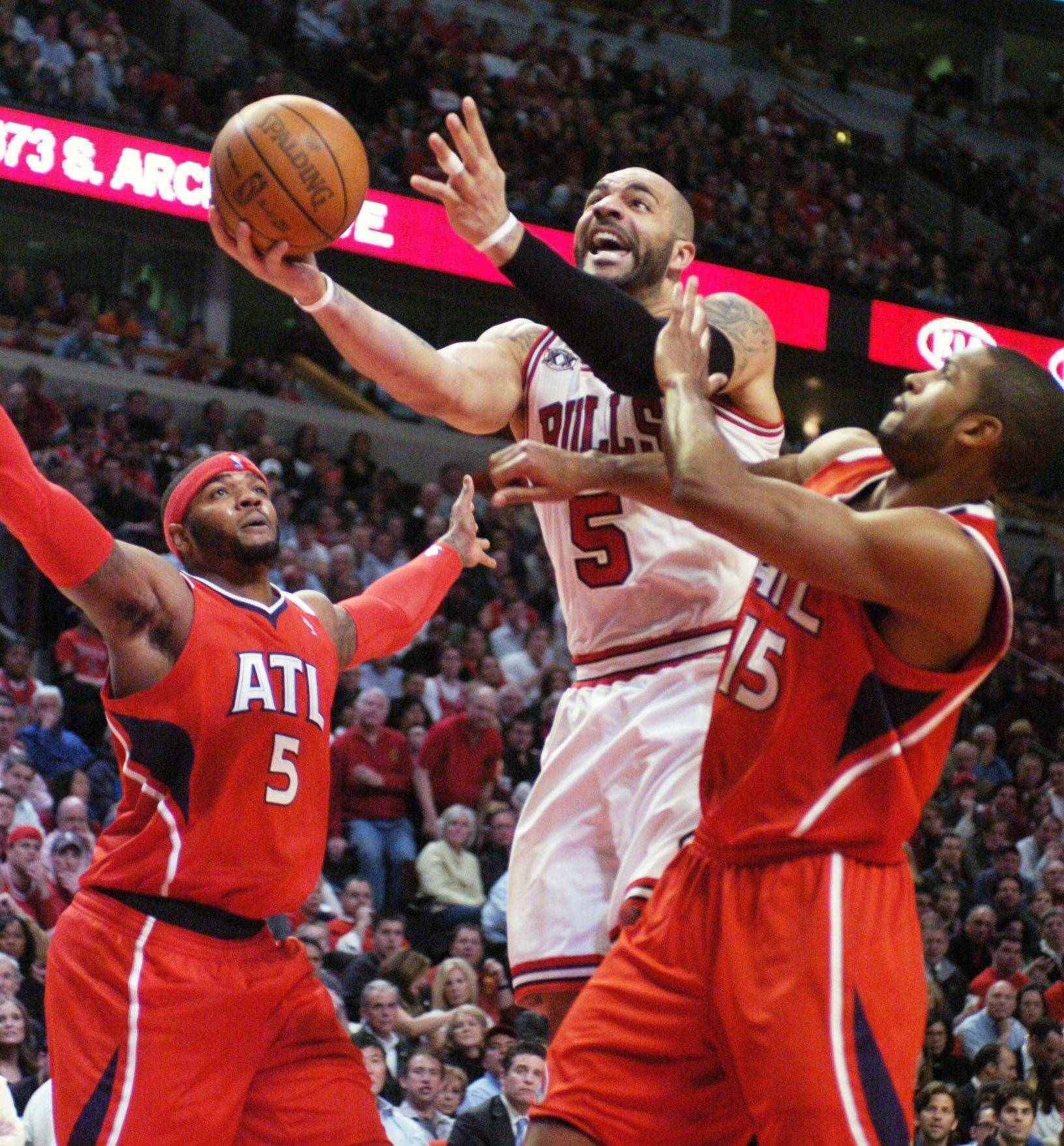 Carlos Boozer of the Bulls drives between Josh Smith, left, and Al Harford of the Hawks during Wednesday's game.