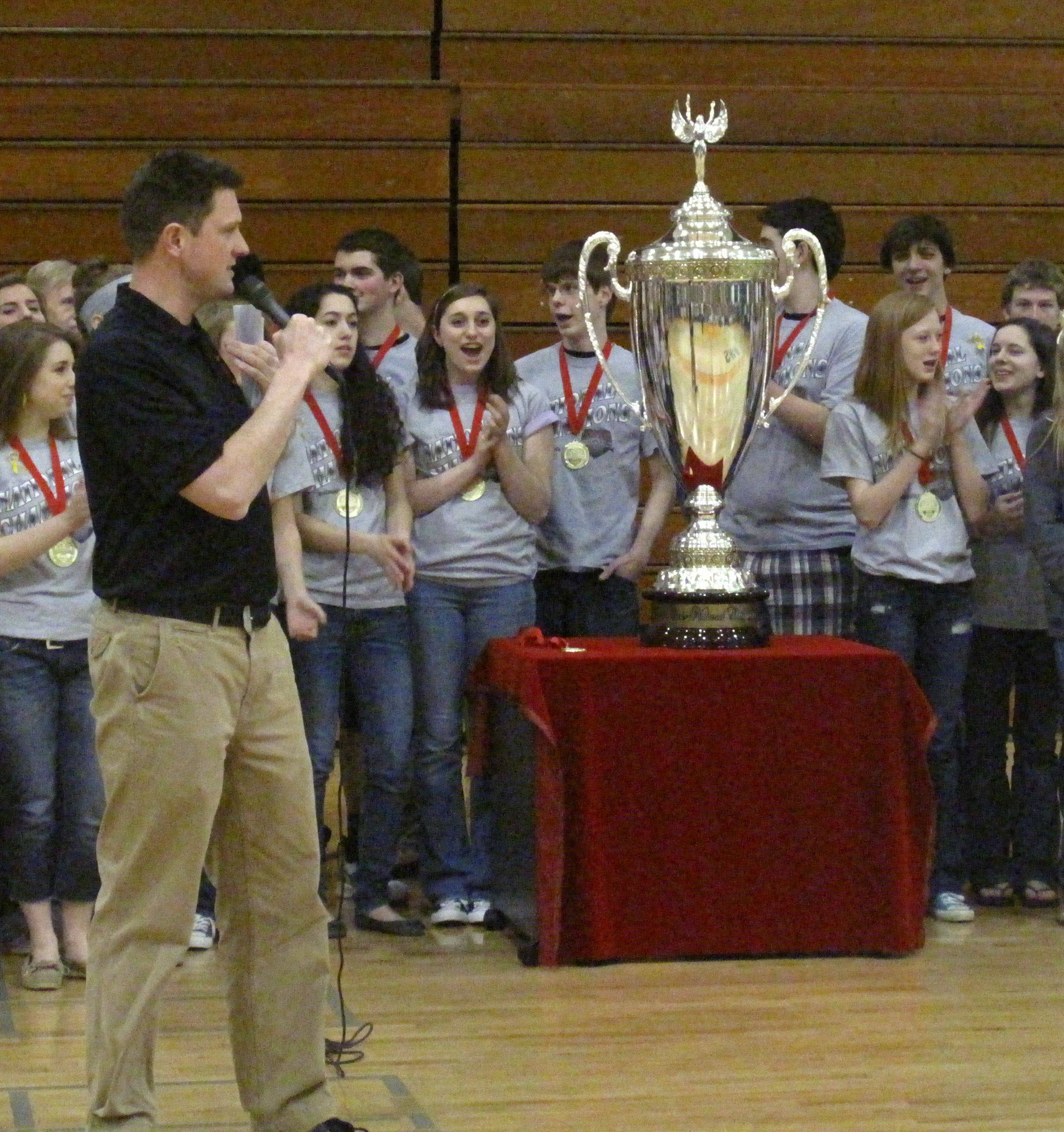 Wheaton Warrenville South High School show choir director John Burlace addresses students in front of his performers and the Show Choir Cup, which his group, the Classics, won at a national competition in Indianapolis.