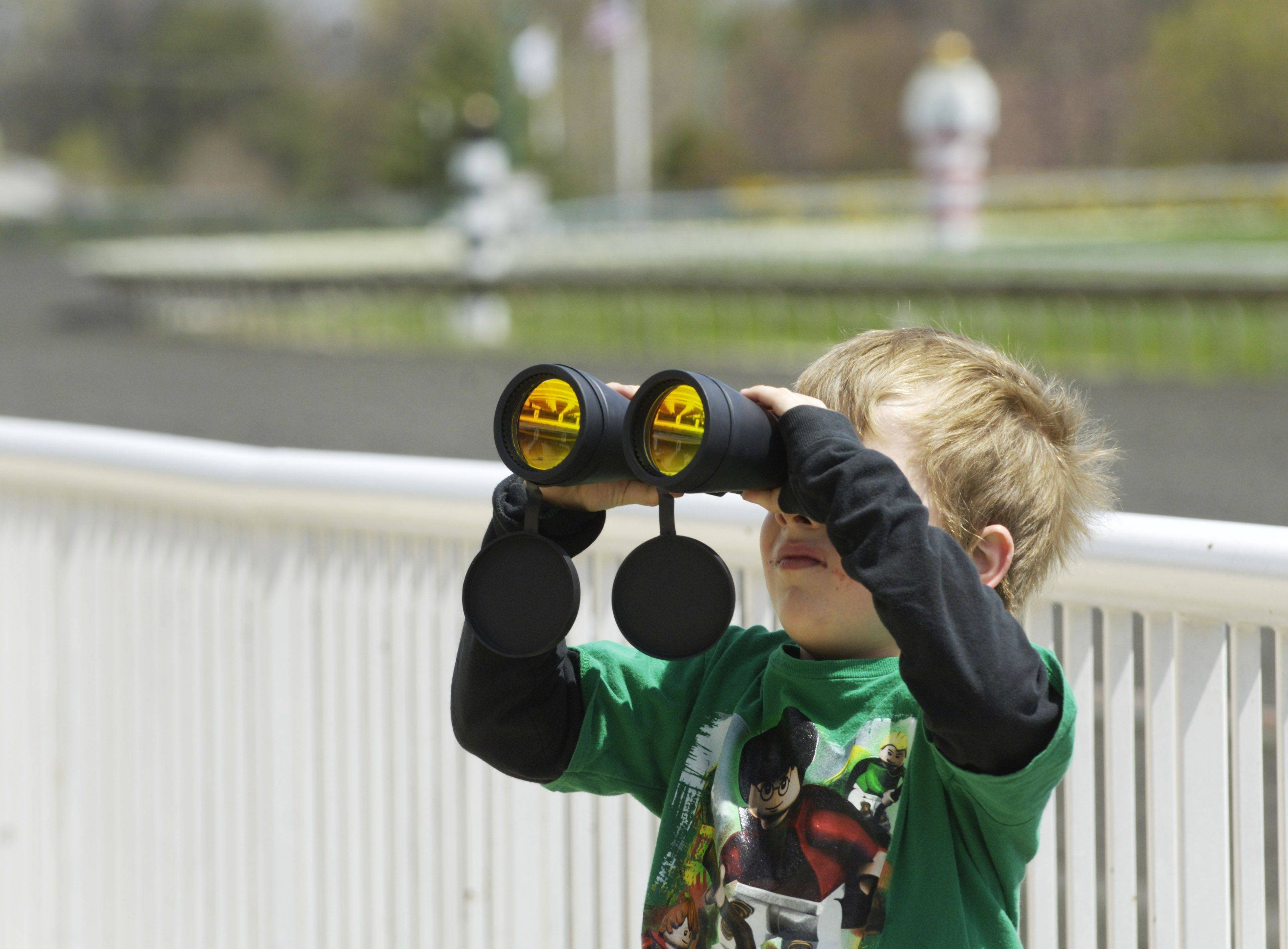 Jacob Ackerley, 5, of South Bend, Ind., tries out his dad's binoculars prior to the start of racing.