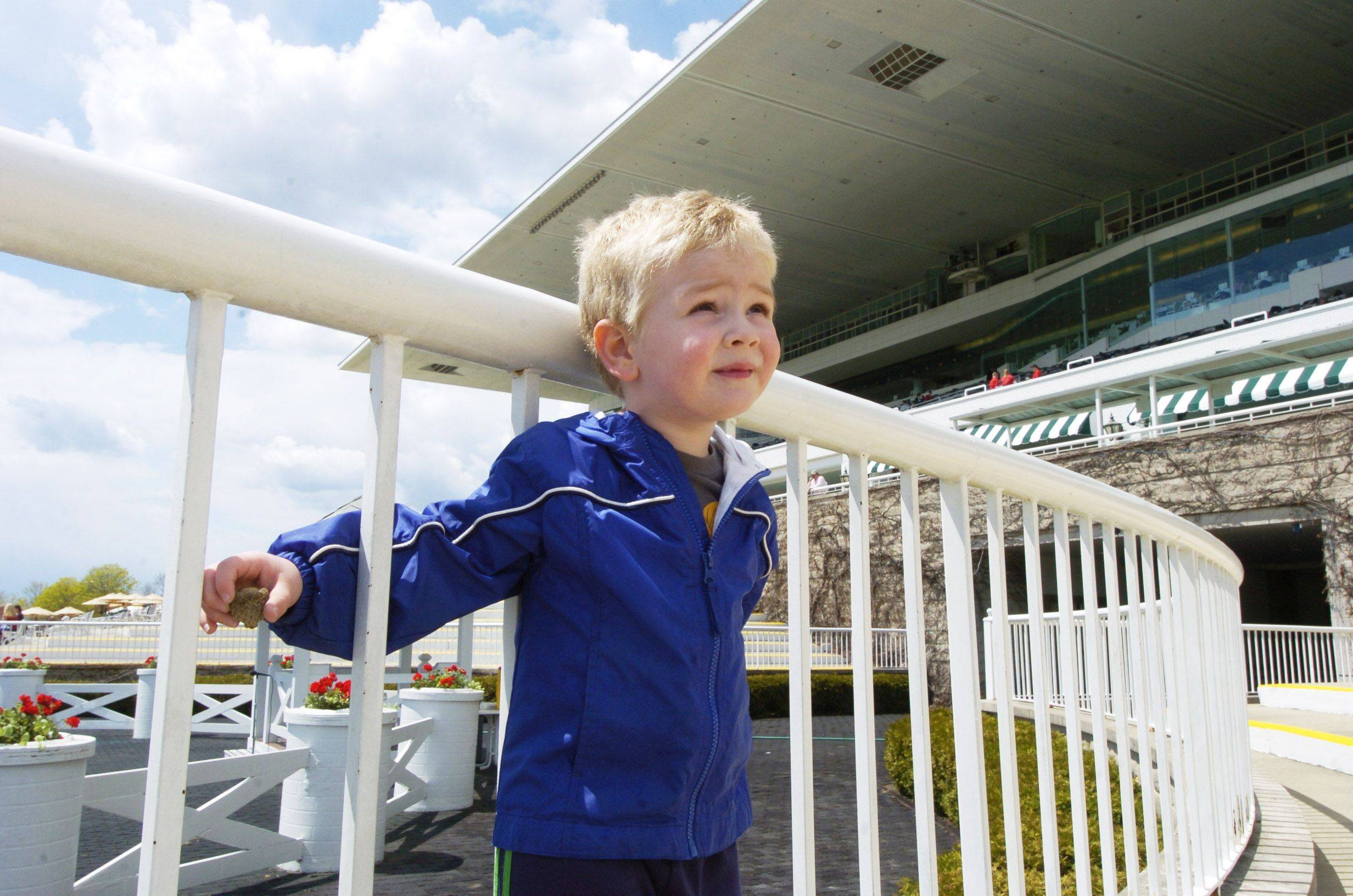 Christian Ottaviano, 3, of Gilberts waits for horses near the winners circle Friday.