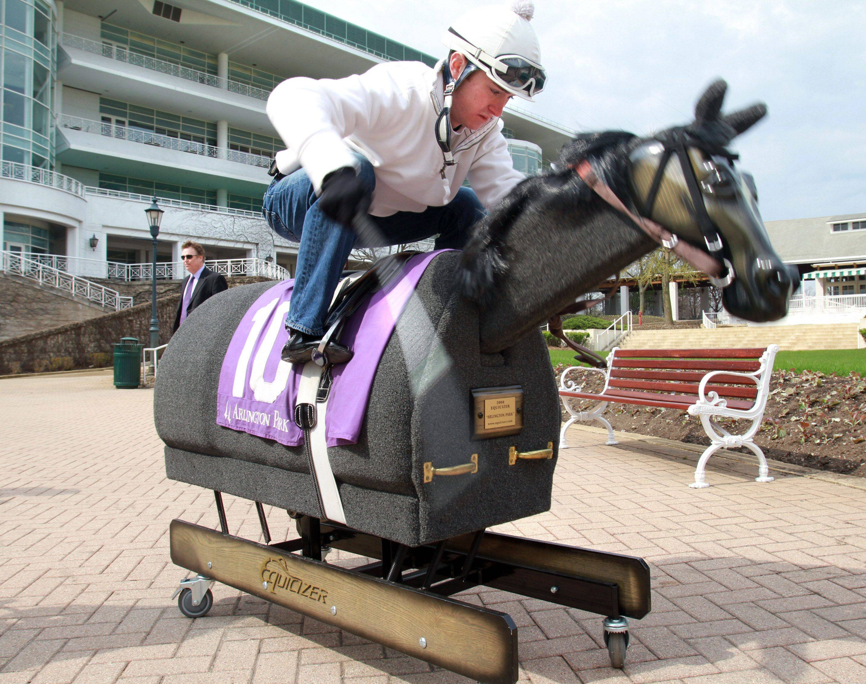 Jockey Josh Molitor, 19, trains on an Equicizer at Arlington Park. Riding the apparatus, which moves like a horse and helps jockeys perfect their style, is hard work, he said.