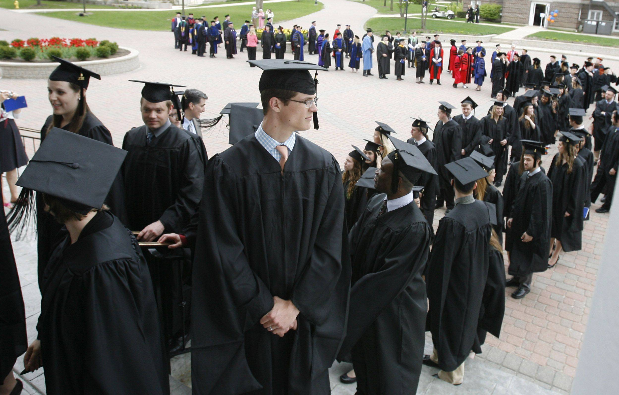 Graduate Student Jon Hughes, center, looks back as he and other graduate students prepare to enter the Edman Memorial Chapel for commencement exercises at Wheaton College.
