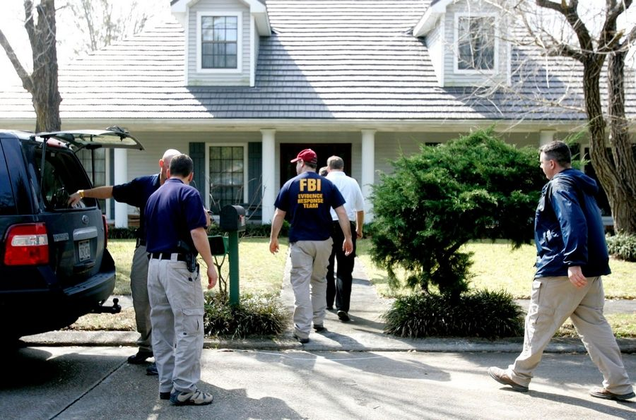 FBI agents search a house in Houma, La. as part of an investigation into Tai Kuo, a businessman. Kuo convinced two U.S. government employees to give him classified information, which he then passed to an official in China. Kuo pleaded guilty to conspiracy to deliver national defense information to China and was initially sentenced to nearly 16 years in prison. That was reduced last summer to five years, thanks to his cooperation with authorities.