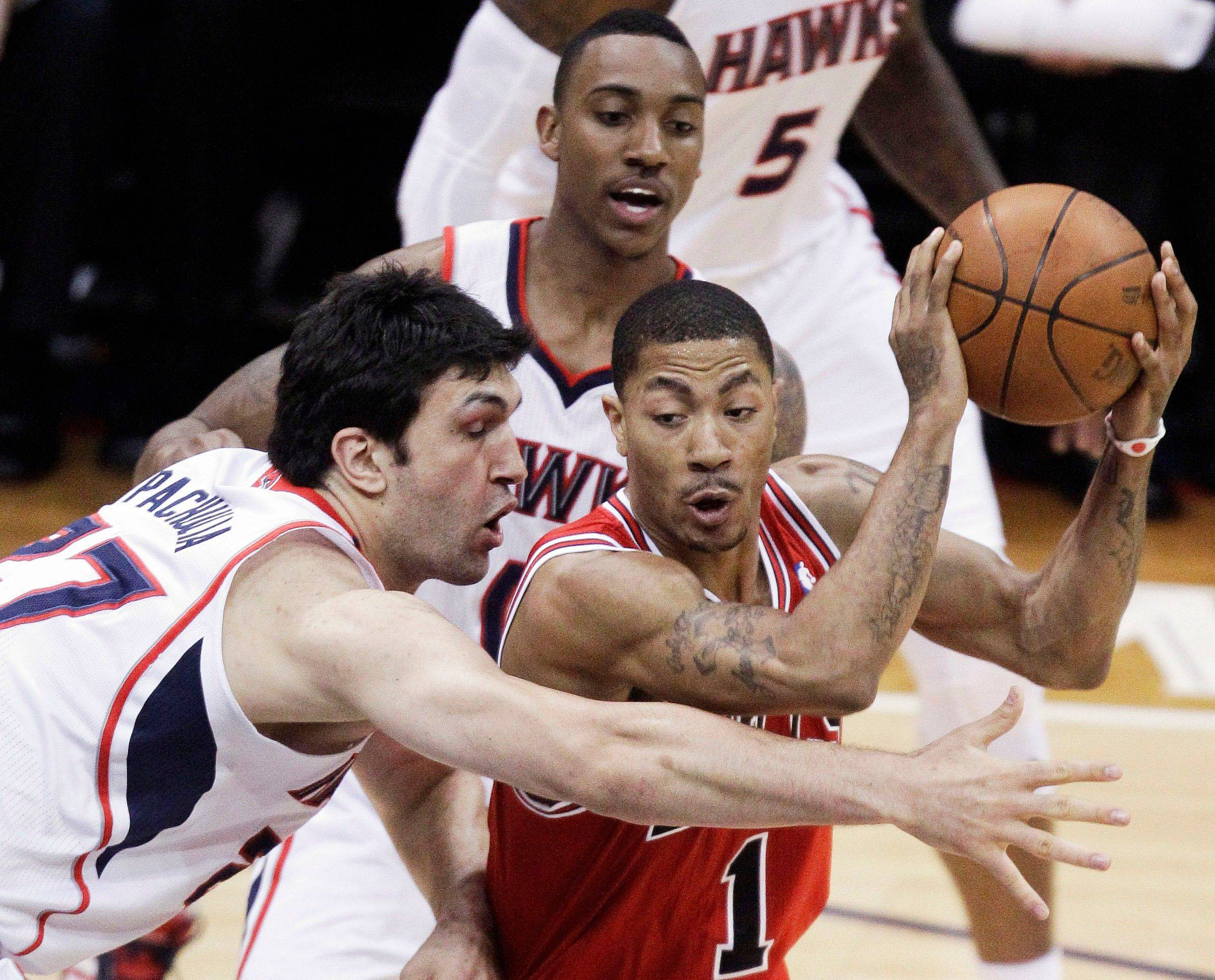 Derrick Rose (1) looks to pass under the defense of Atlanta Hawks guard Jeff Teague (0) and center Zaza Pachulia (27) in the second quarter of Game 4.