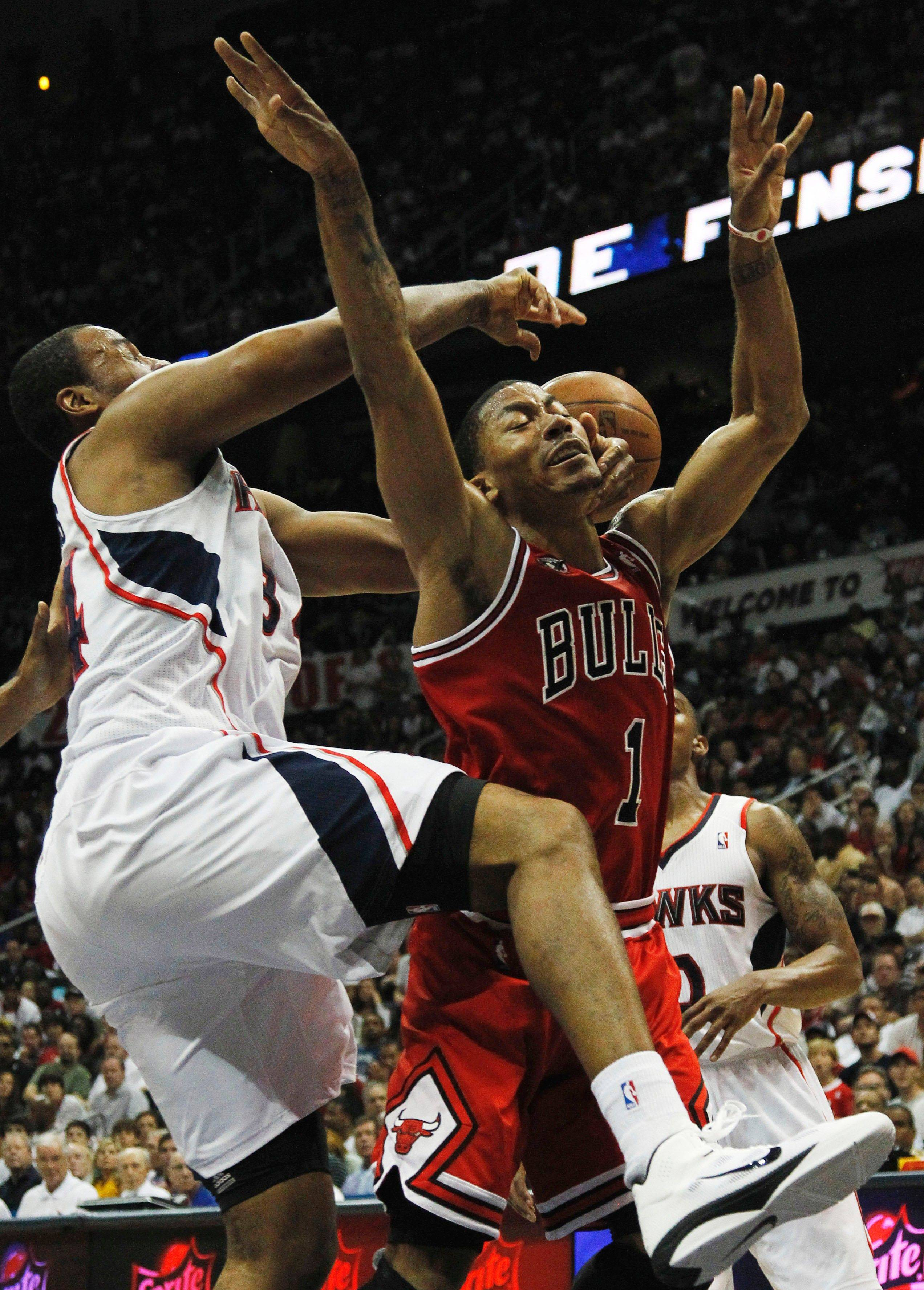 Derrick Rose (1) has his shot blocked by Atlanta Hawks center Jason Collins, left and guard Jeff Teague, right, in the third quarter of Game 4.