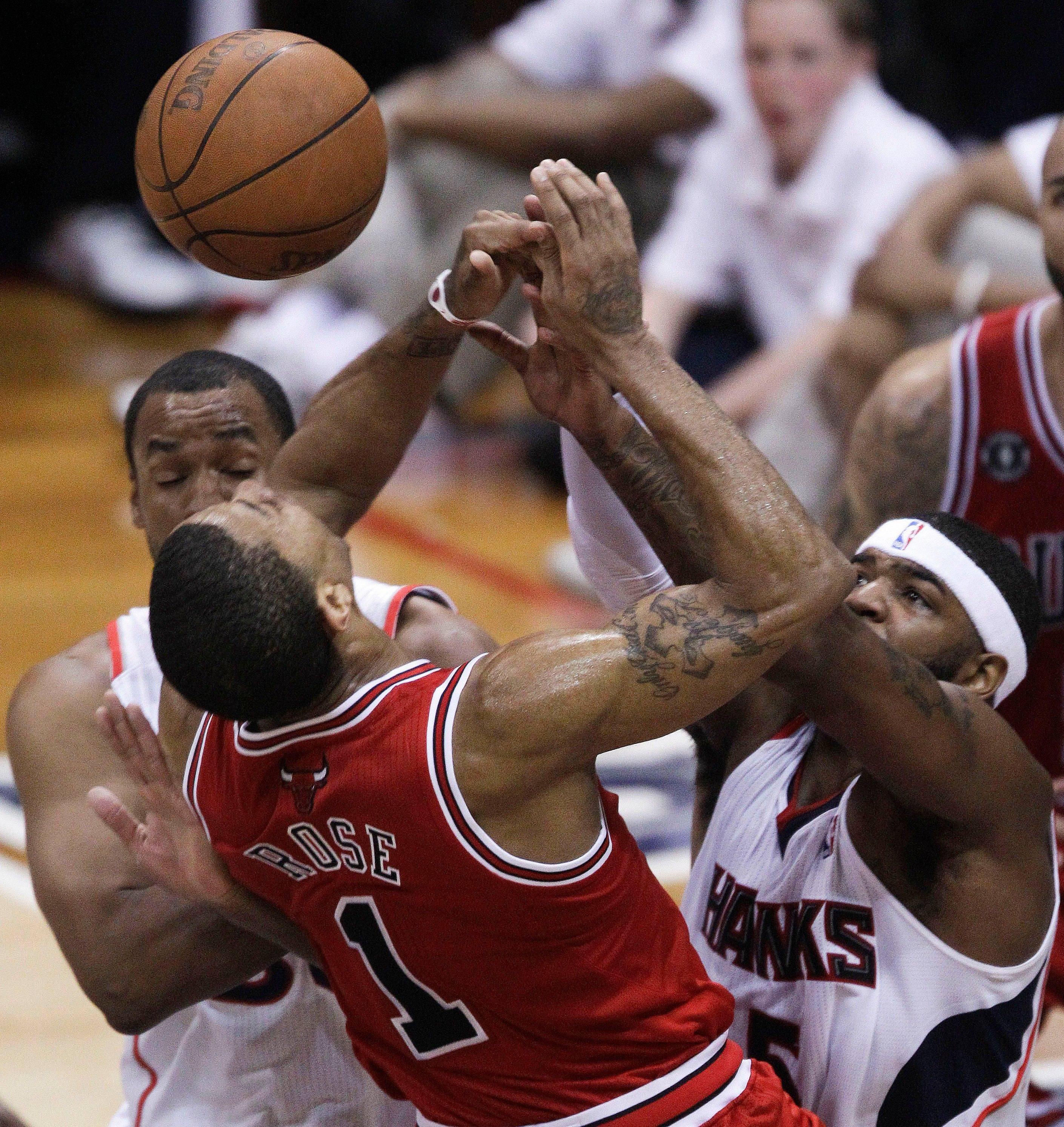 Derrick Rose (1) is denied by Atlanta Hawks power forward Josh Smith, and Jason Collins, left, in the third quarter.