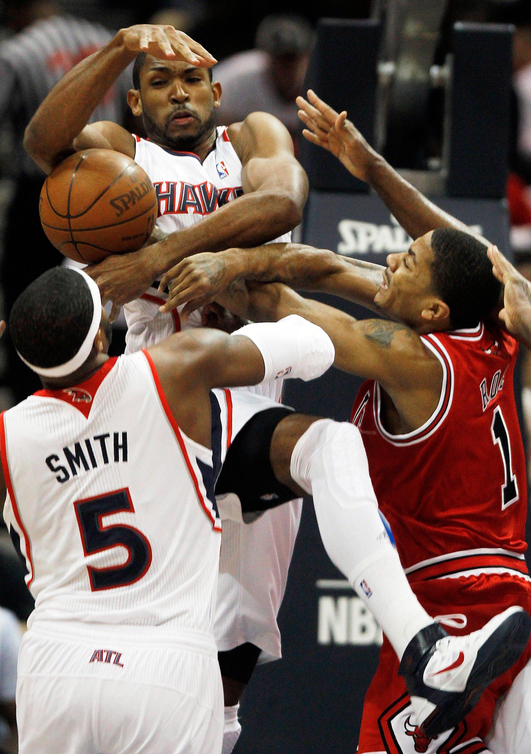 Atlanta Hawks center Al Horford, top center, vies for a rebound against Derrick Rose (1) as power forward Josh Smith (5) defends in the first quarter.