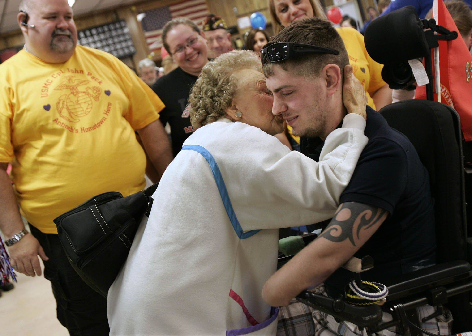 U.S. Marine Cpl. John Peck receives a kiss from Eleanor Hauser.