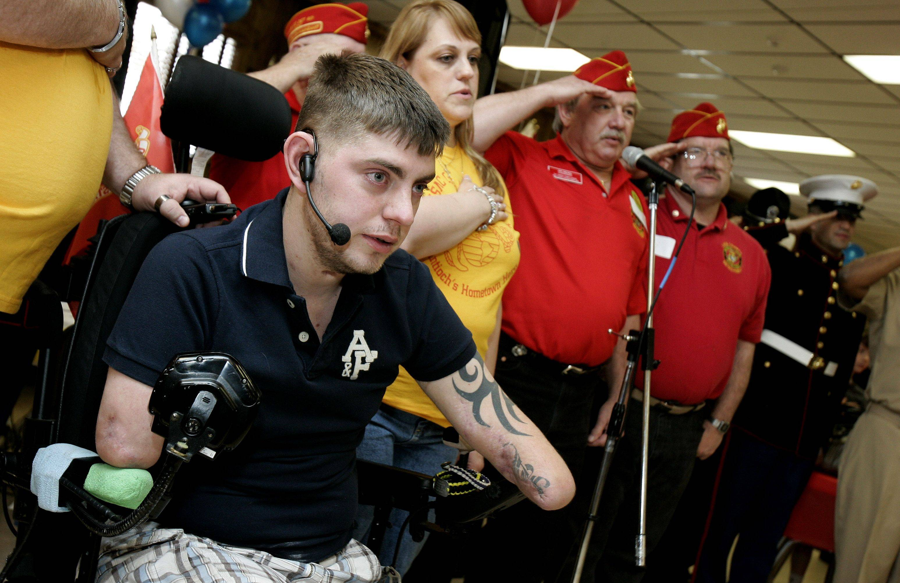 U.S. Marine Cpl. John Peck recites the Pledge of Allegiance, surrounded by the Marine Corps League 801, as he was honored in Antioch Monday after returning from serving in Afghanistan. Peck lost four limbs in Afghanistan after stepping on an IED.