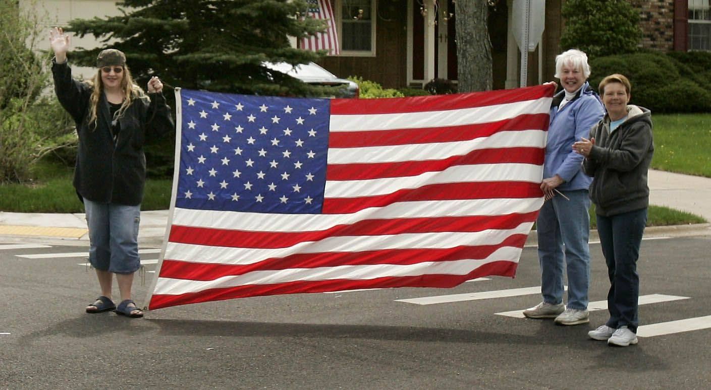 Antioch residents wave a flag for U.S. Marine Cpl. John Peck during a parade in his honor in Antioch Monday.