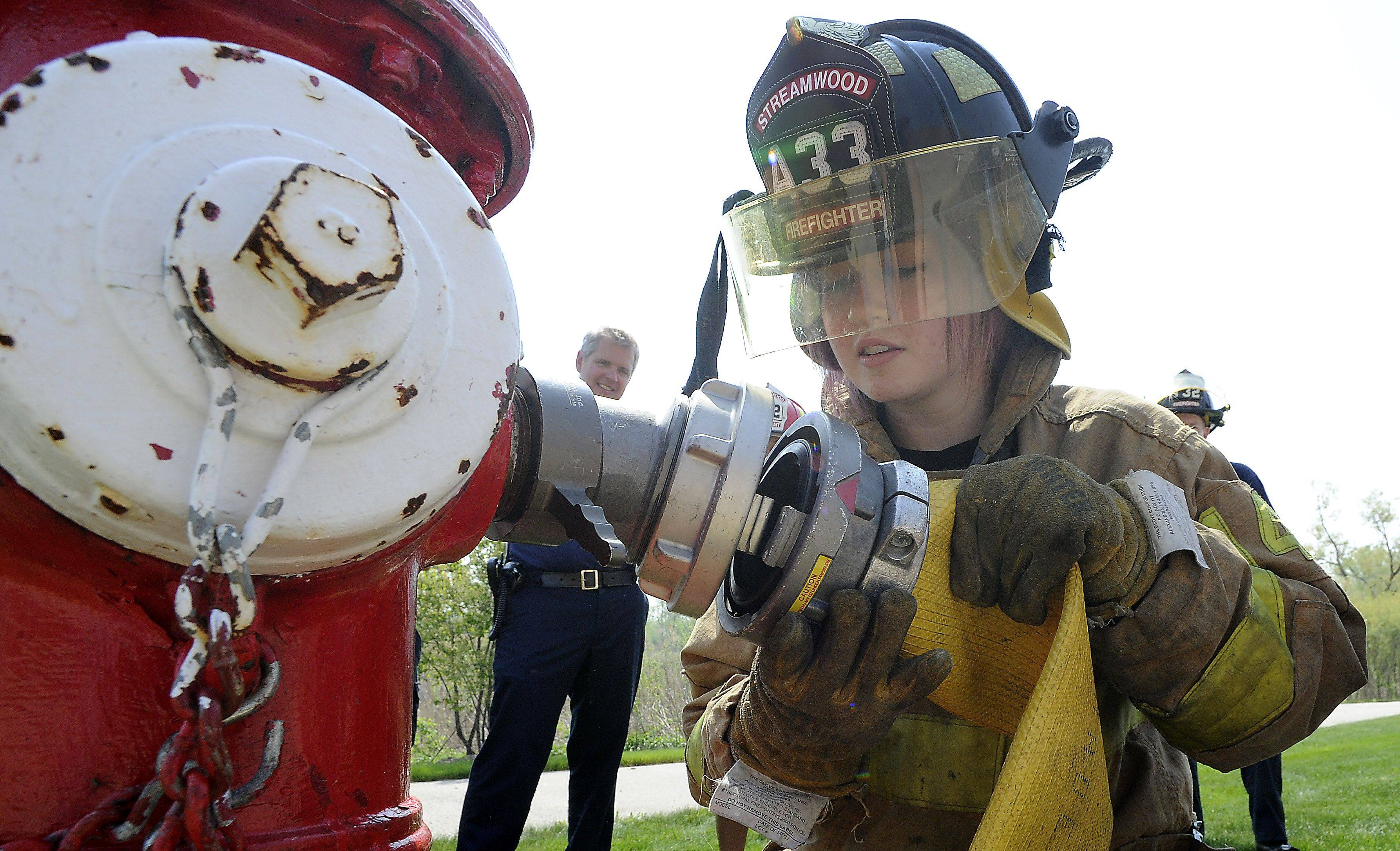 Streamwood High School senior Veronica Henderson shadows a Streamwood firefighter Wednesday during the school's 30th annual Student Government Day.
