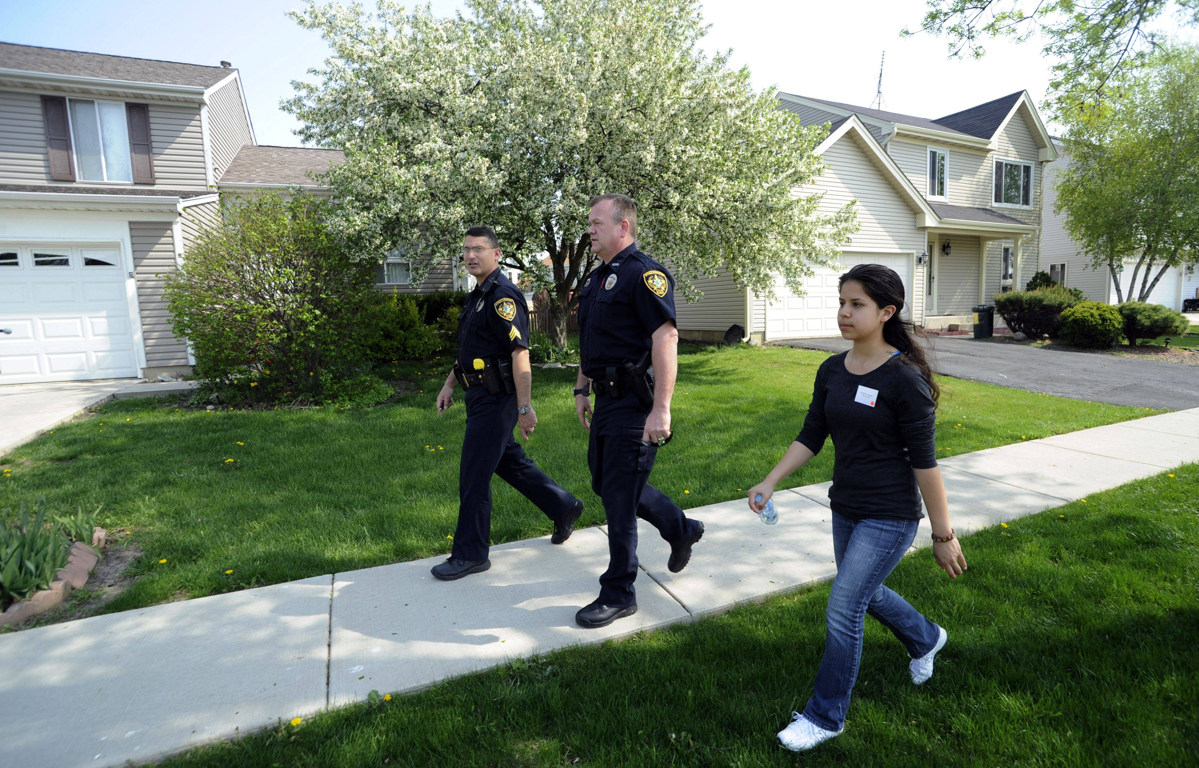 Streamwood High School senior Gabriela Chairez, 17, accompanies Streamwood patrol Sgt. Ed Valente and Officer Steve Millar as they walk the beat during the school's 30th annual Student Government Day.
