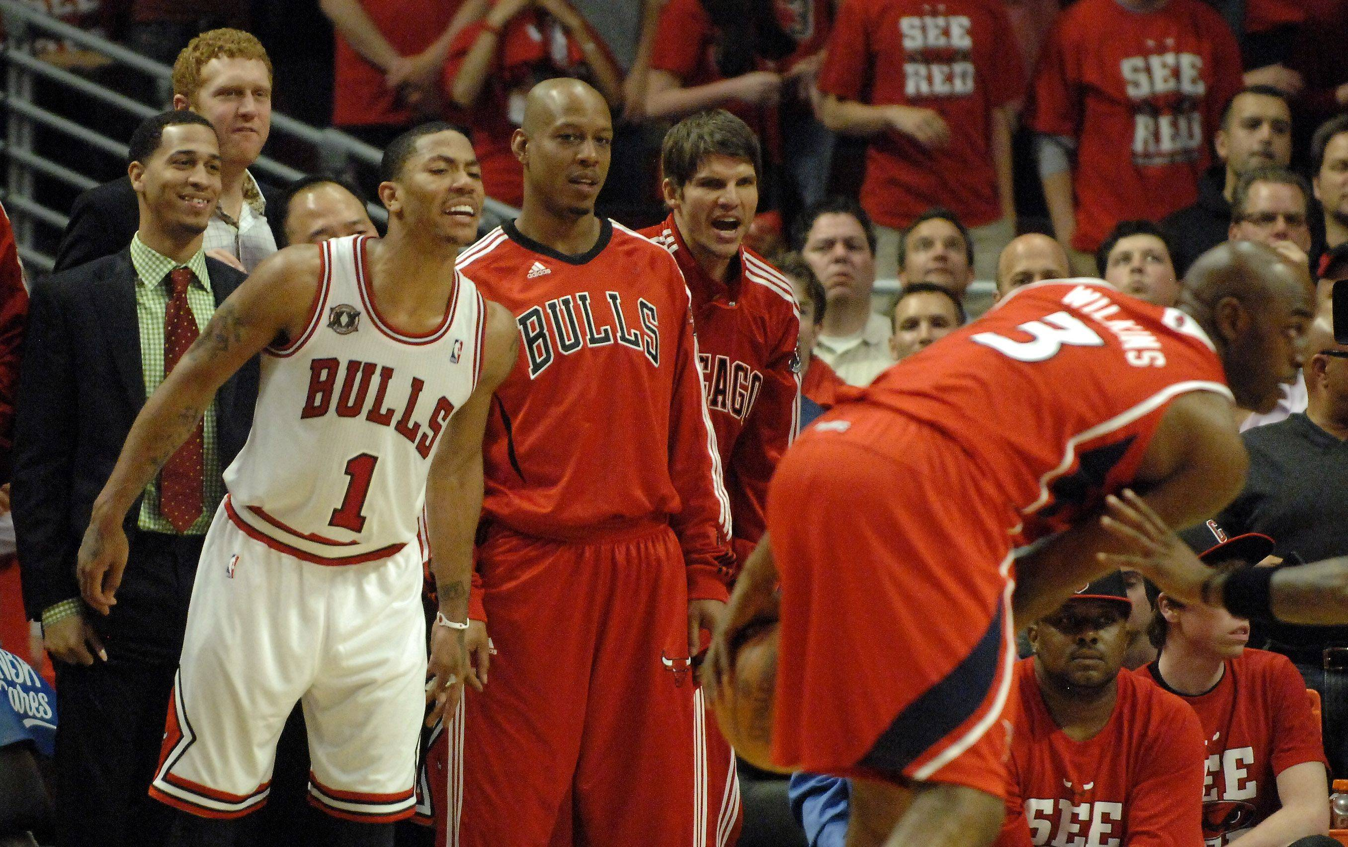 The Bulls' Derrick Rose and his teammates cheer from the bench in the final minute of game 5 against the Atlanta Hawks in Chicago Tuesday.