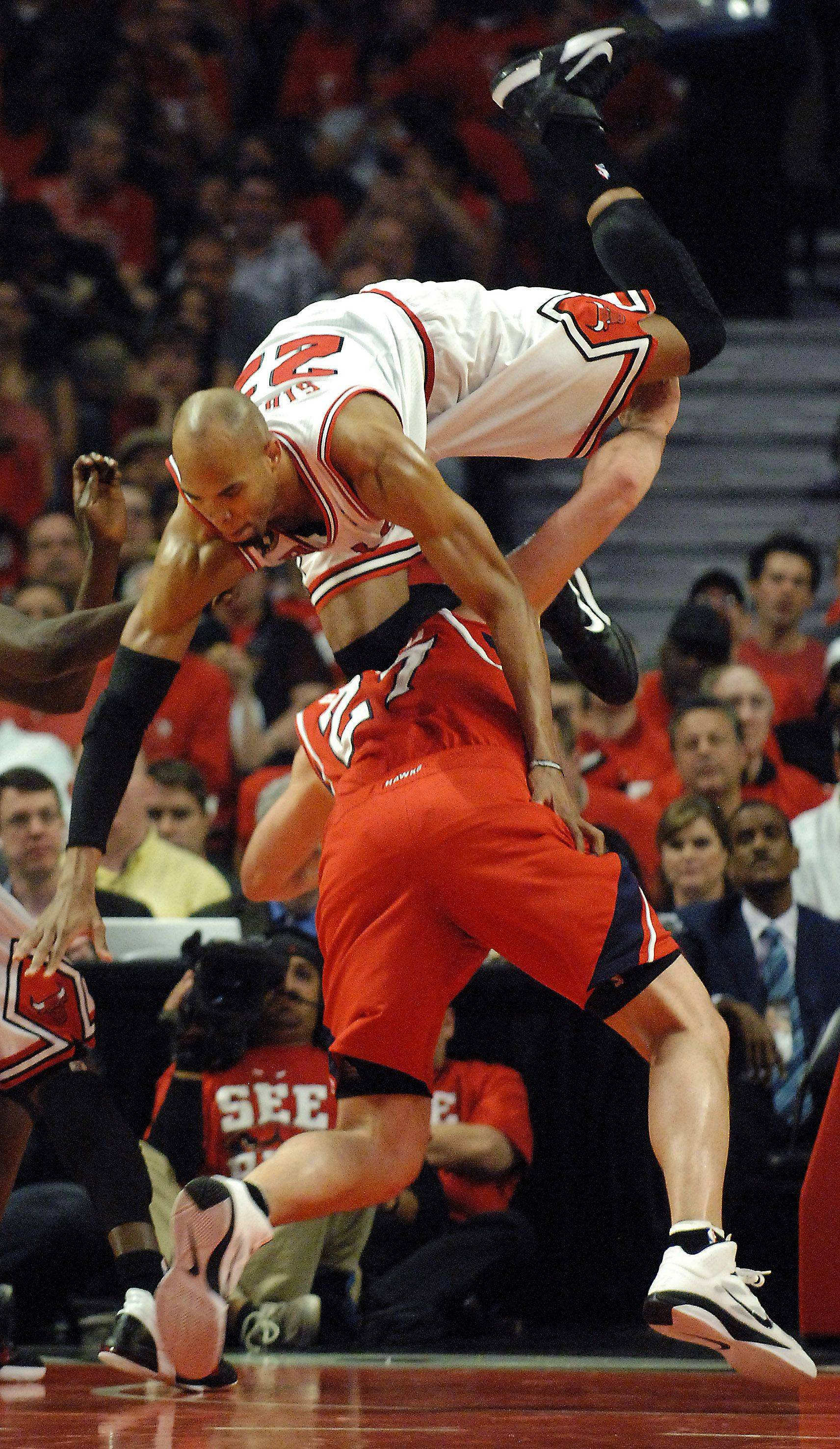 Chicago Bulls forward Taj Gibson flips over Atlanta Hawks center Zaza Pachulia and is called for a foul Tuesday.