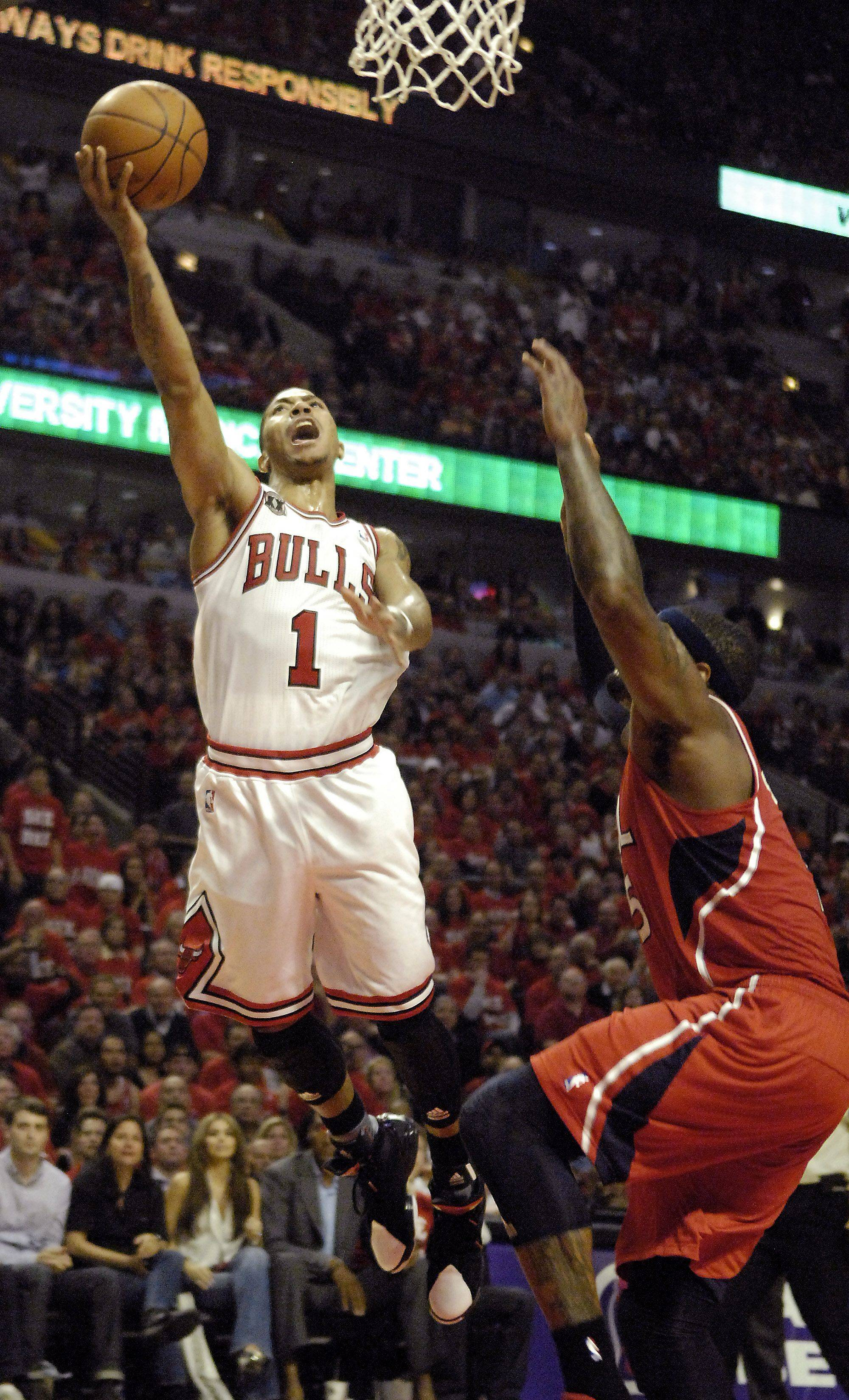 Chicago Bulls' Derrick Rose drives to the hoop and lays it up over Atlanta Hawks' Josh Smith in game 5 of the NBA Eastern Conference semifinals.