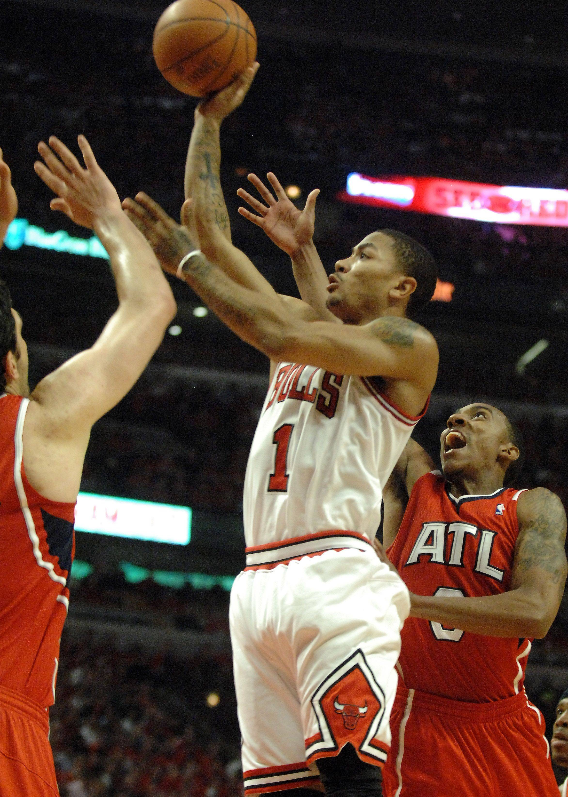 The Bulls' Derrick Rose drives past Atlanta's Jeff Teague, right, and over center Zaza Pachulia Tuesday.